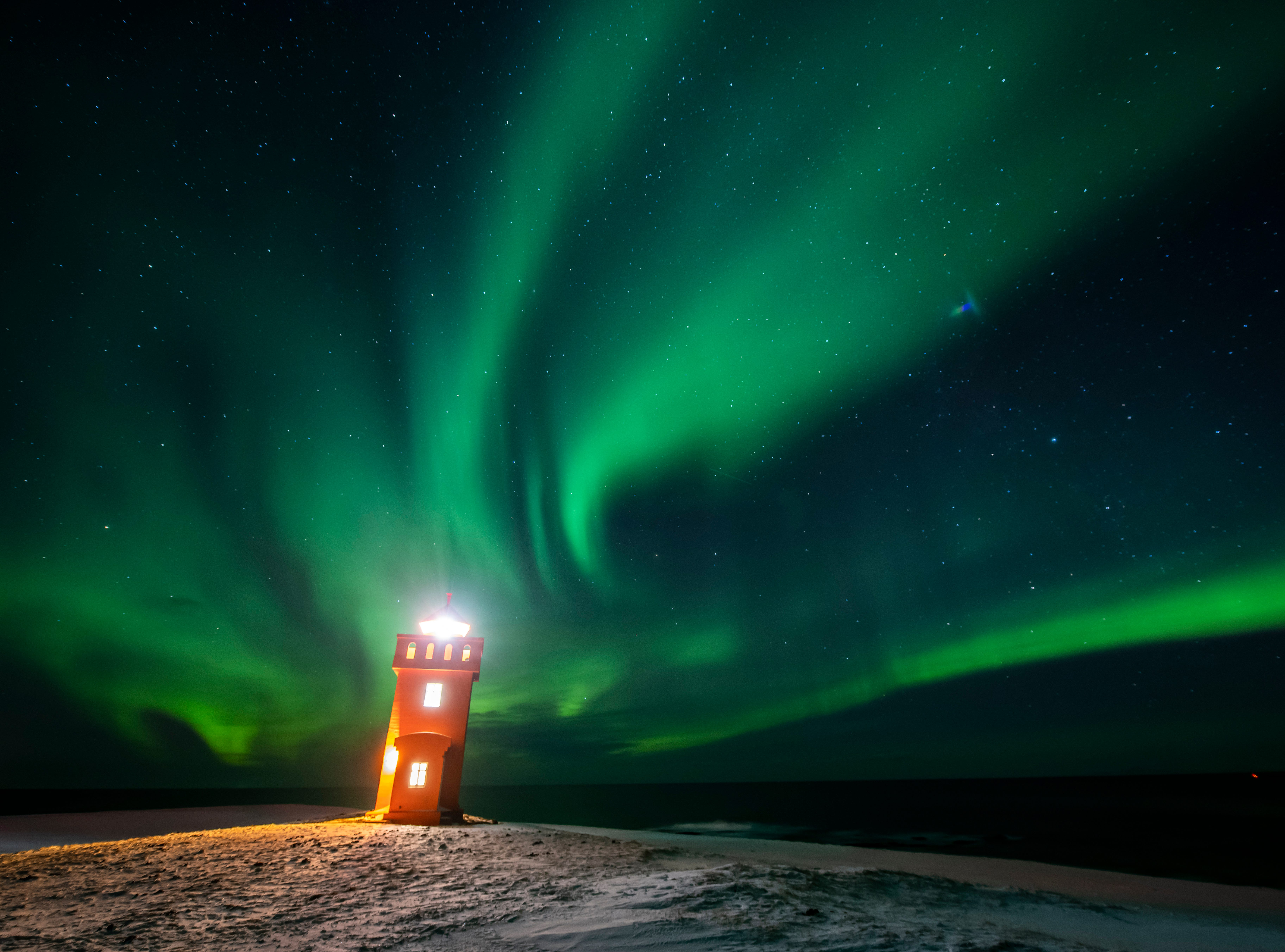 Aurora borealis or northern lights are visible in the sky above a lighthouse to the village of Grundarfjorour in Iceland. Aurorae are caused by the interaction between energetic charged particles from the sun and gas molecules in the upper atmosphere of the earth, about 100 kilometres up.
