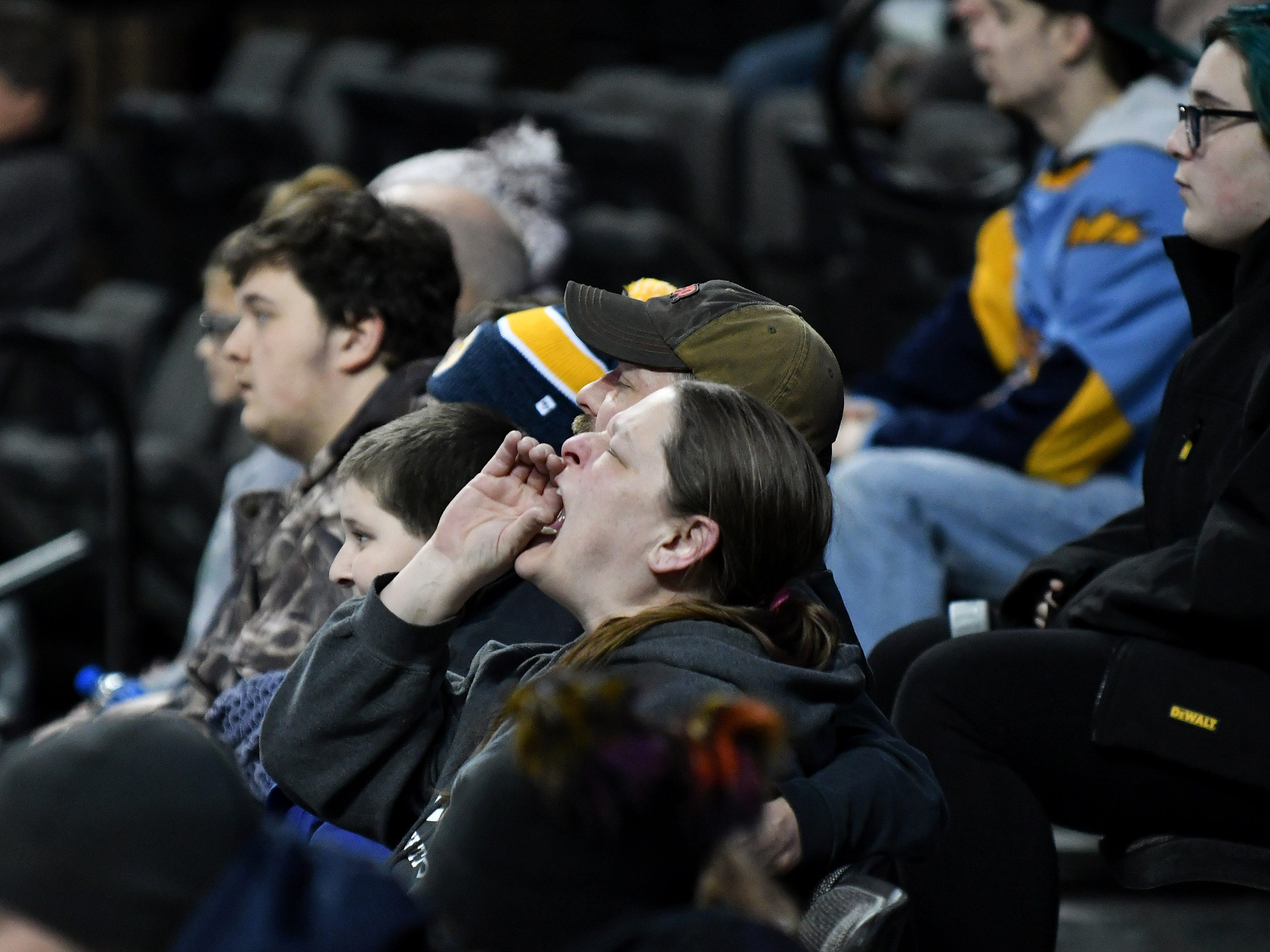 Wendy Laubenthal of Perrysburg, Ohio, hollers in the first period.  Laubenthal was at the game with Jon Burkett, to her right; son, Paul Laubenthal, 12; and seated behind her is her daughter, Emily Laubenthal, 15, far right.