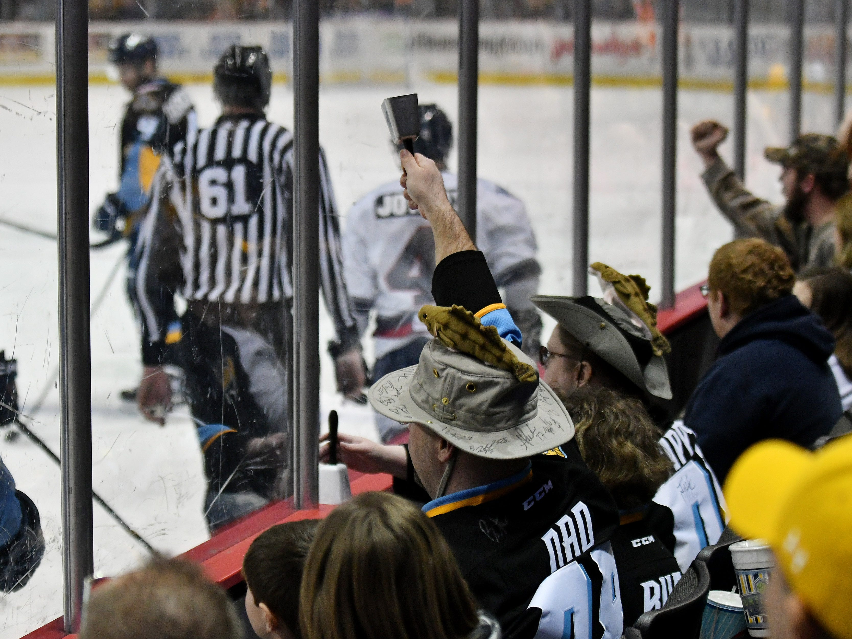 Michael McInerney of Sylvania, Ohio, makes noise with his cowbell in the second period.  McInerney and his wife, Tammy, are wearing hats that Michael customized with walleye pinned to the tops. Seated between them is their daughter, Katie McInerney, 9.