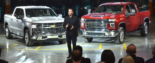 Rich Scheer, Director, Exterior Design, Chevy Trucks, talks between the Silverado 1500, left, and Silverado HD.  The HD trucks come in five new trims, from the basic work truck to the top-level High Country with a chromed-out grille.