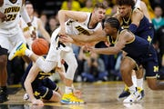 Michigan guard Zavier Simpson, right, tries to steal the ball from Iowa guard Jordan Bohannon during the second half of last week's 74-59 loss.