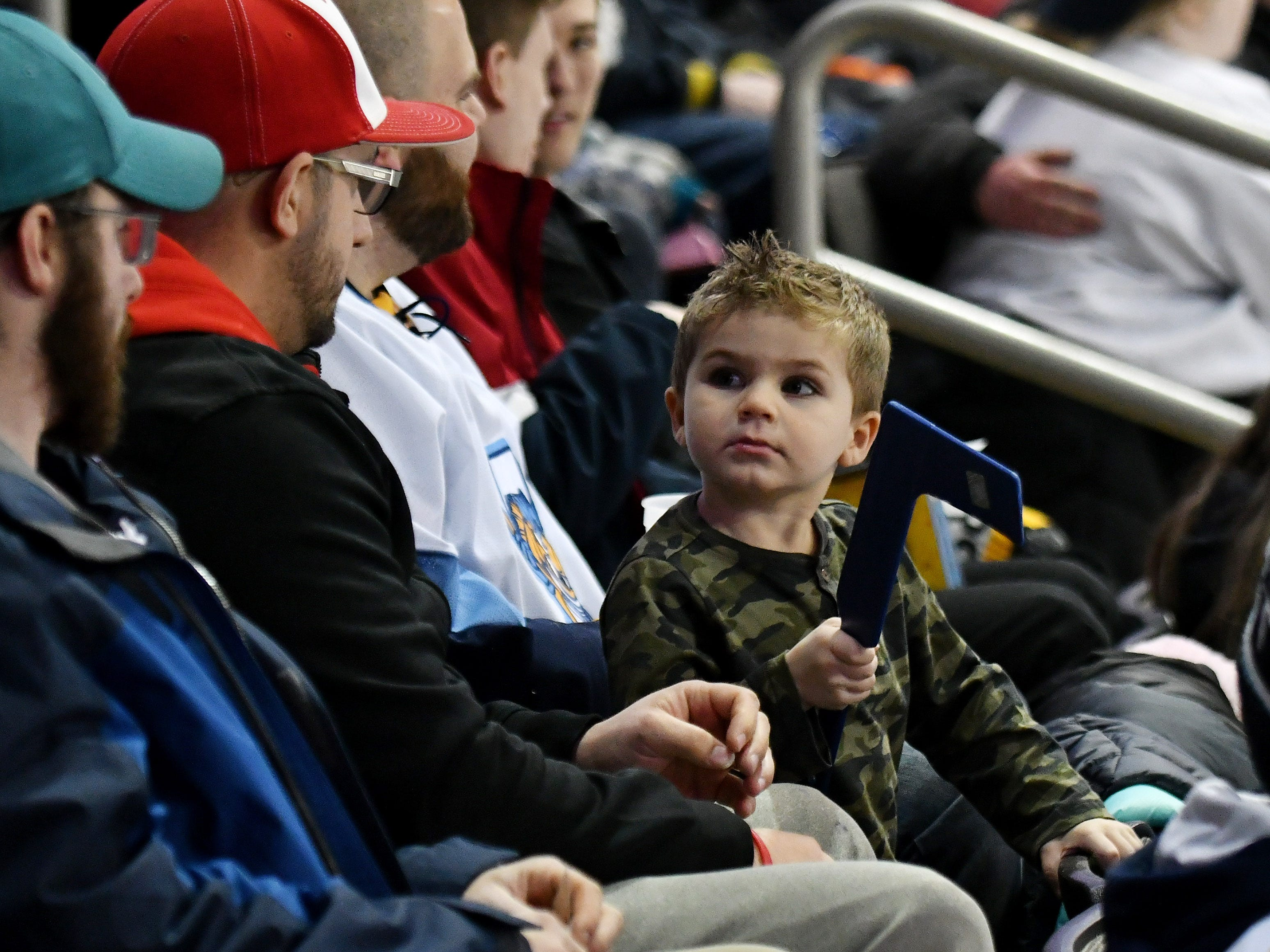 Zain Baroudi, 3, of Toledo looks over to Ray Leroux, left, a friend of his father, in white shirt, and Zach Baroudi in the first period.