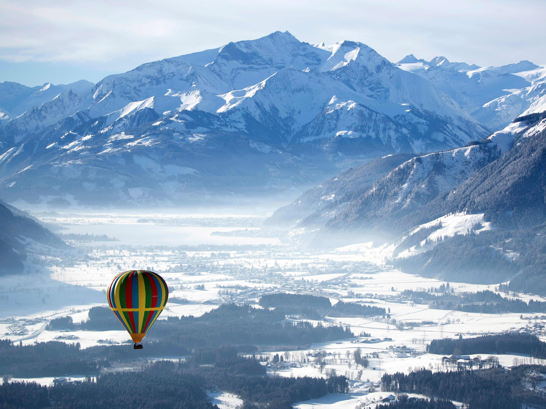 A hot air balloon makes his way above Zell am See, Austria, Tuesday, Feb. 5, 2019.