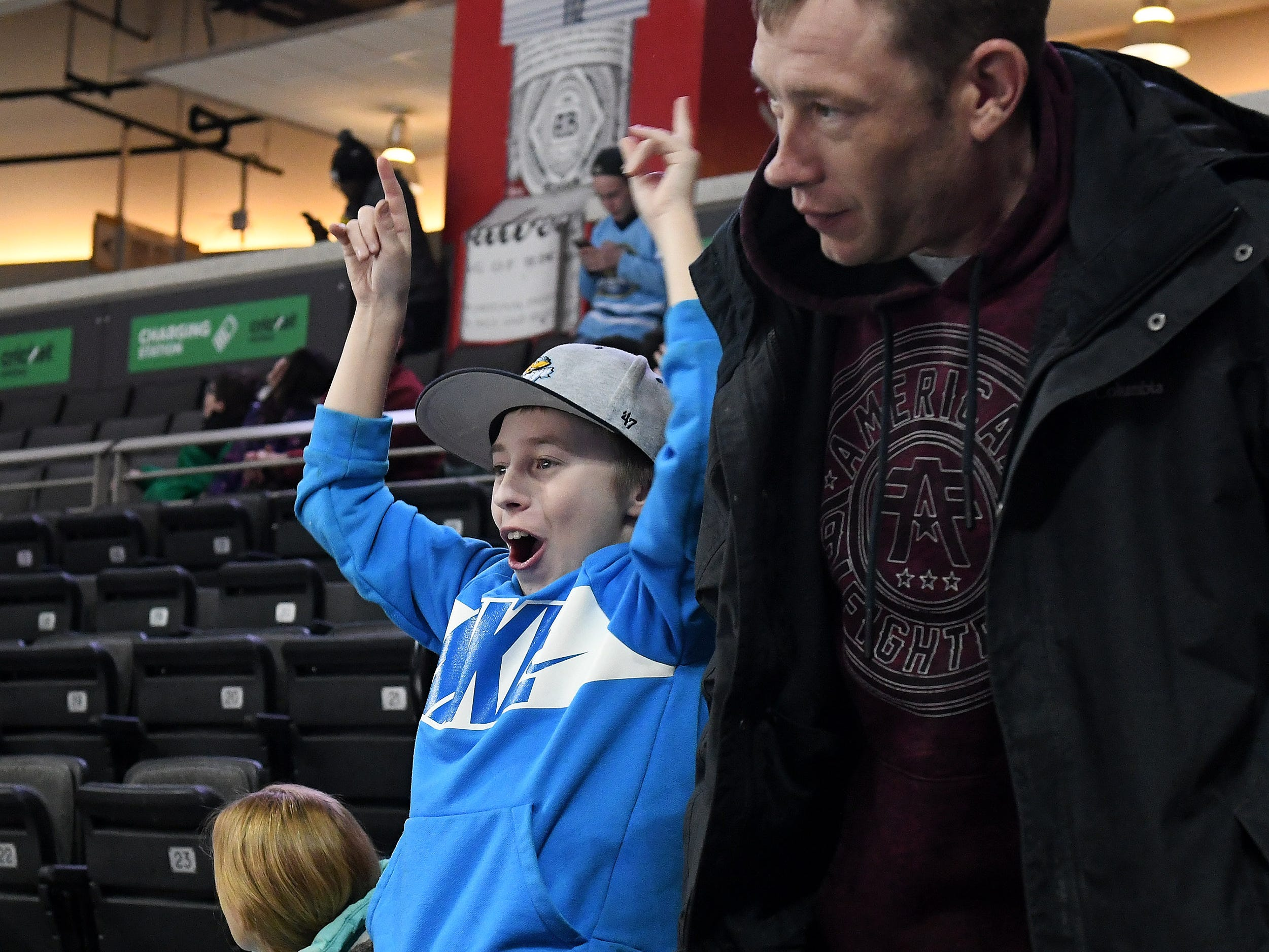 Ryan Wright, 12, of Toledo cheers next to his father, Jamey Wright, after the Walleye score a go-ahead goal in the third period.