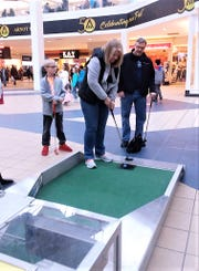 Participants take part in the annual Compeer mini-golf fundraiser at the Arnot Mall.