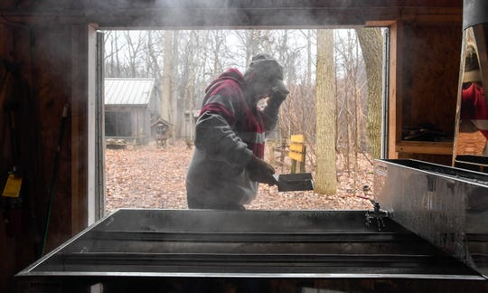 """LeeAnne Bruner skims foam off of the boiling maple tree sap, Bruner has worked volunteered at the park's """"sugar shack"""" cooking down the syrup for thirty years Thursday, February 5, 2019."""