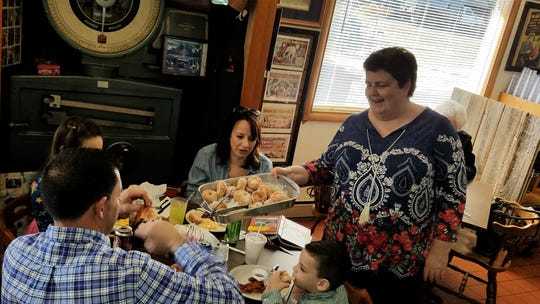 Owner Evelyn Miller presents a table of regular customers with a pan of hot, just-fried donuts at the Windy Hollow Restaurant.