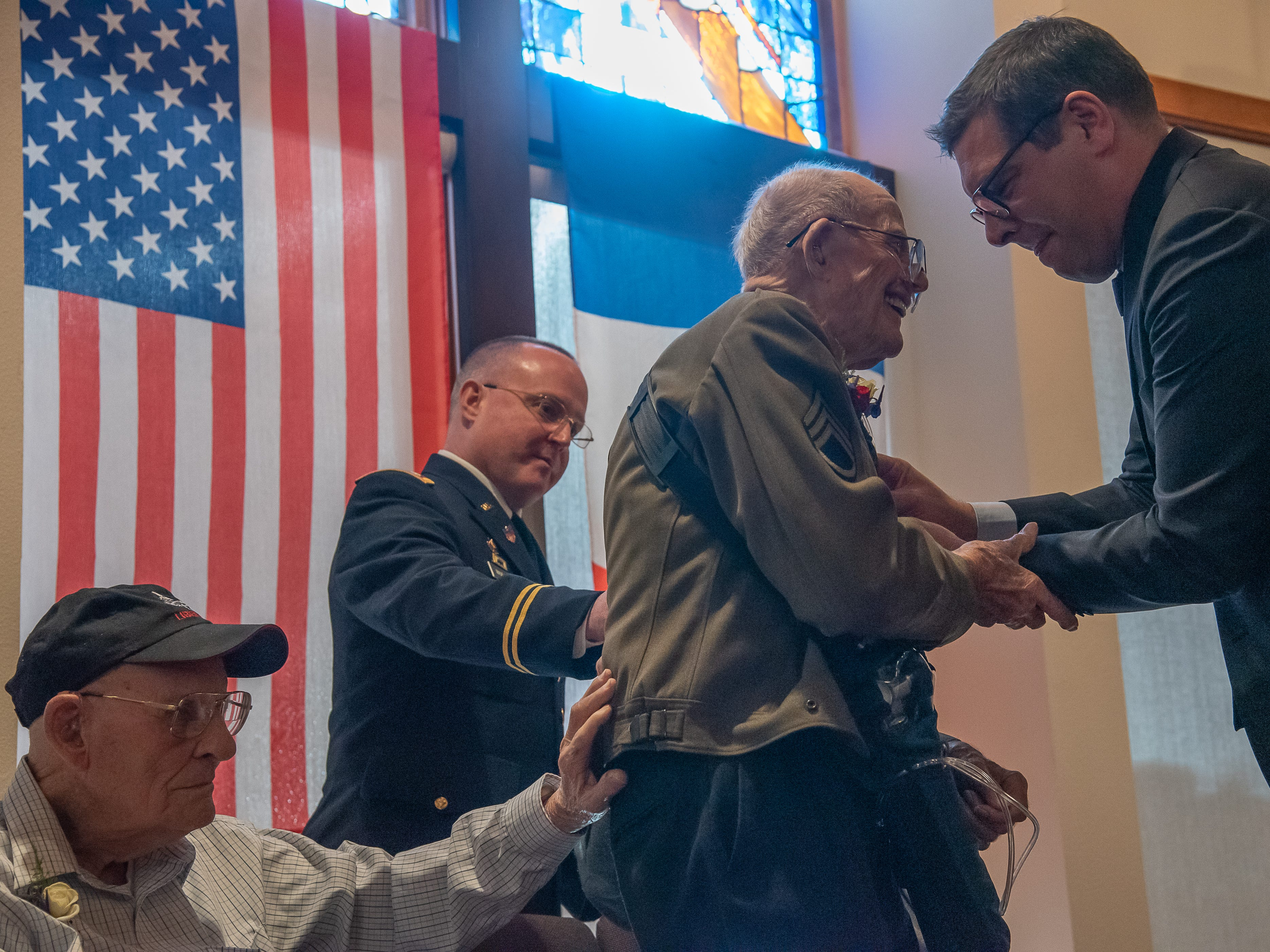 Fort Collins resident and World War II veteran Bill Powell gives fellow veteran Philip Daily a hand of support as he rises to receive the French Legion of Honor Medal from Christophe Lemoine, Consulate of France, on Monday, February 4, 2019, during a ceremony at the Good Samaritan Water Valley Resort in Windsor. Ltc. Frank Huffman stands behind Daily, also offering a hand of support.