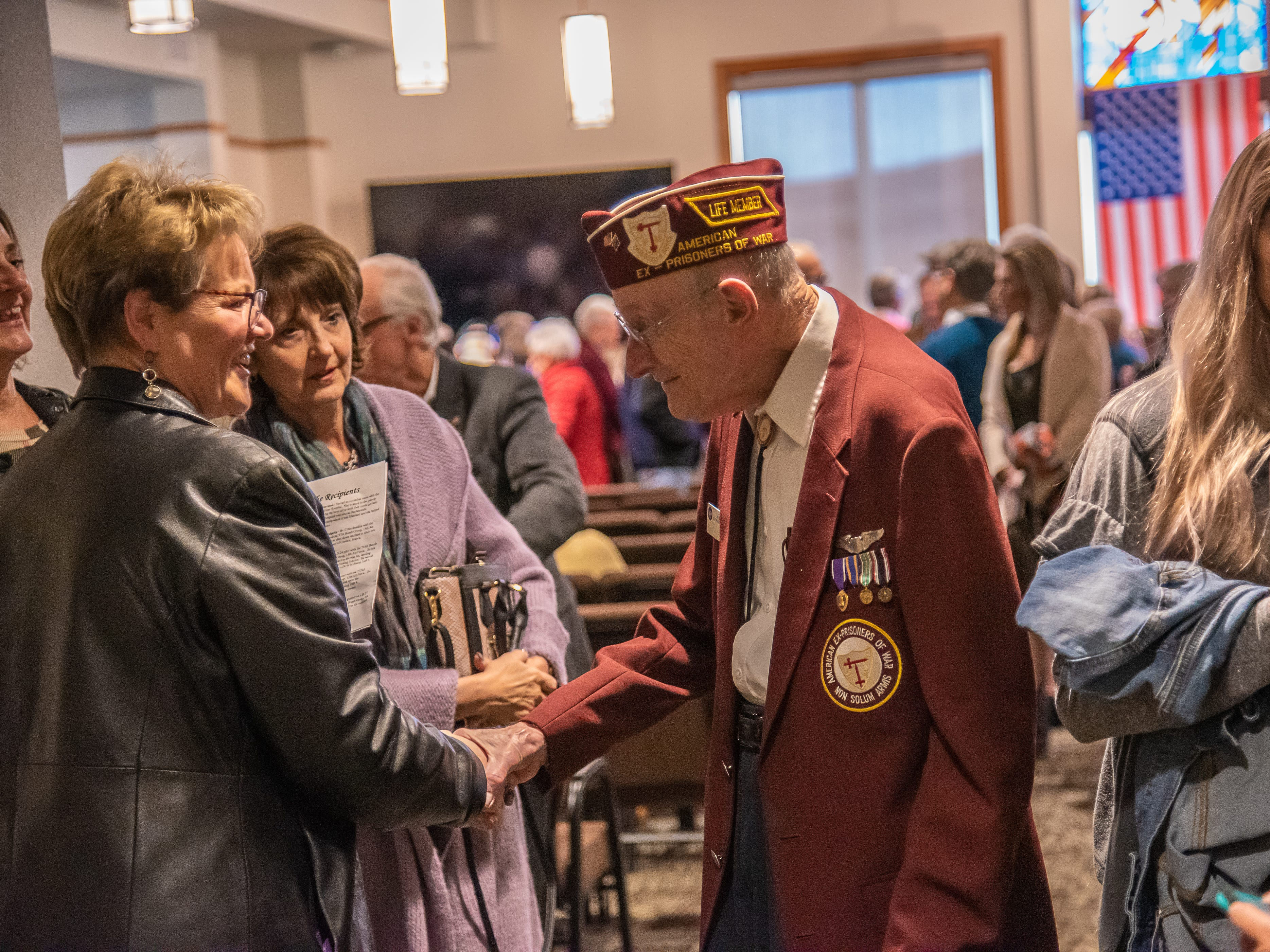World War II veteran Clayton Nattier, resident of Lakewood, shakes hands with attendees of a Legion of Honor Medal ceremony on Monday, February 4, 2019 at  the Good Samaritan Water Valley Resort in Windsor.  Nattier was a POW in the prison camp Stalag Luft 1.