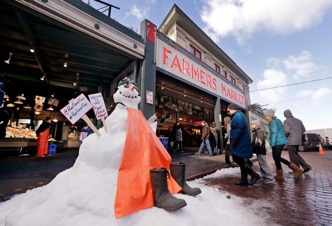 A snow sculpture is dressed as the fish mongers working behind as people walk into the Pike Place Market in near-freezing weather Tuesday, Feb. 5, 2019, in Seattle. Winter weather closed schools and disrupted travel across much of the West, with ice and snow stretching from Seattle to Arizona. The Pacific Northwest shivered Tuesday under colder-than-normal conditions as snow and treacherous conditions led to another day of school closures.
