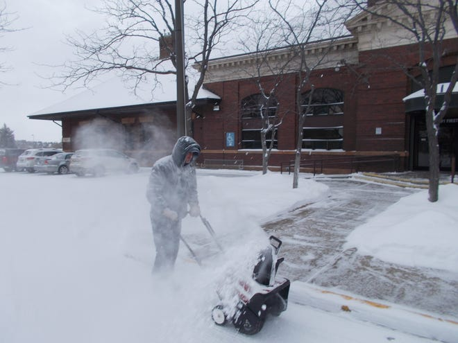 Adam Langel clears the walks around Energy West in Great Falls Tuesday as a cold snap continues.