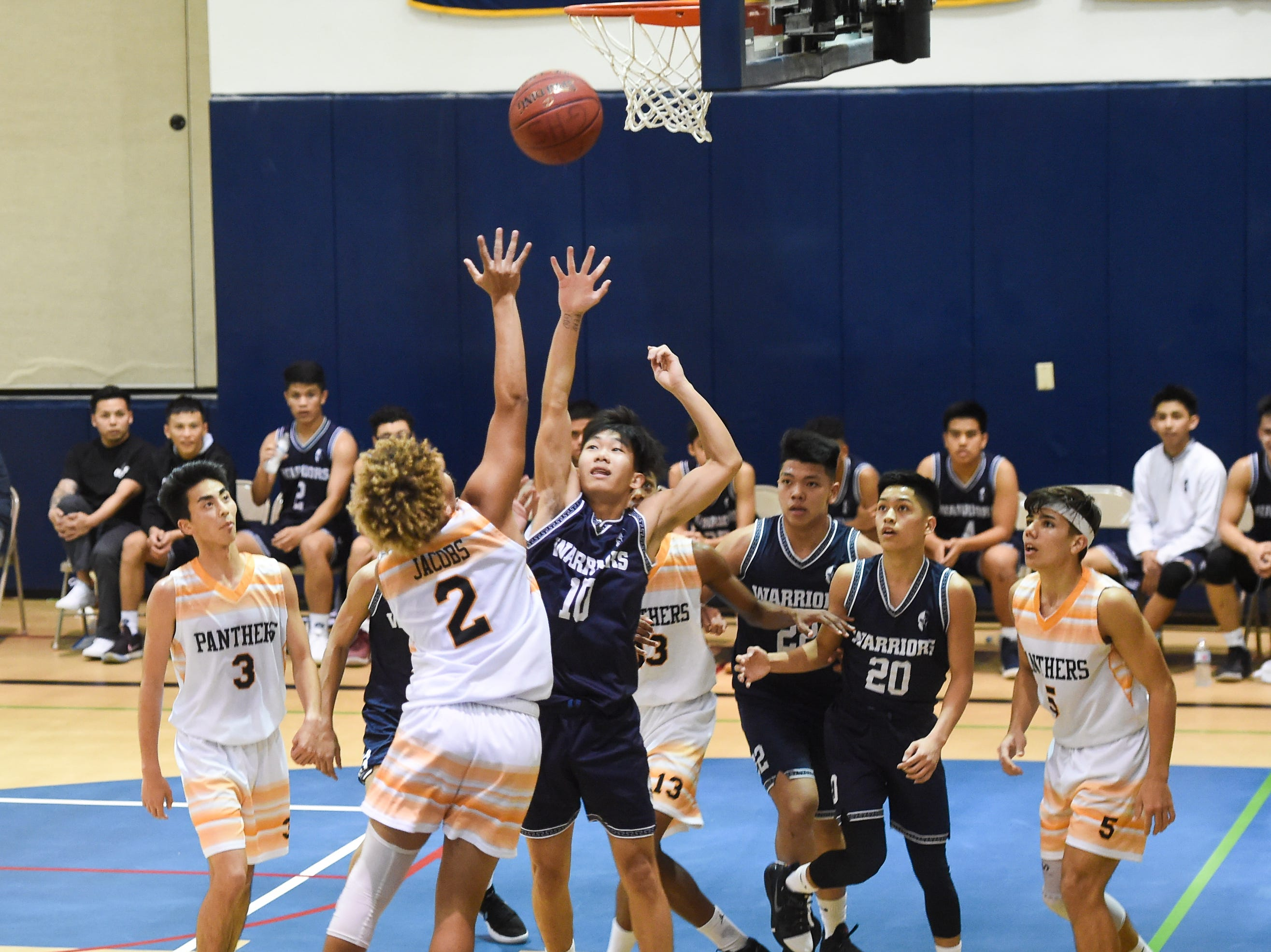 Guam High player Travon Jacobs (2) attempts a shot over St. Paul defenders during their IIAAG Boys' Basketball game at the Guam High School Gym, Feb. 5, 2019.