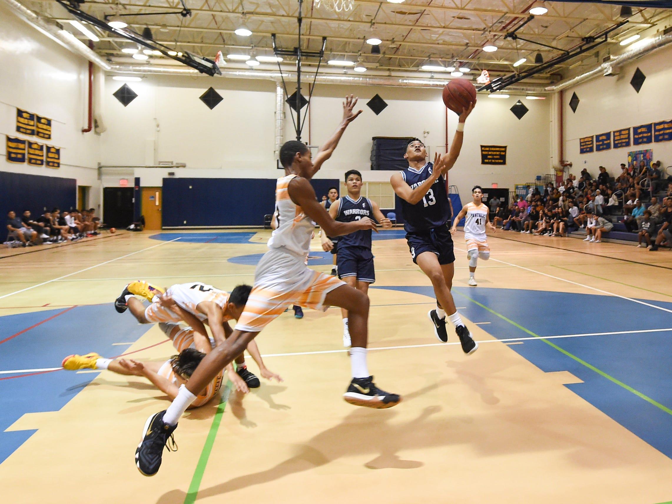 St. Paul player Jahmar White (13) attacks the rim during a IIAAG Boys' Basketball game at the Guam High School Gym, Feb. 5, 2019.