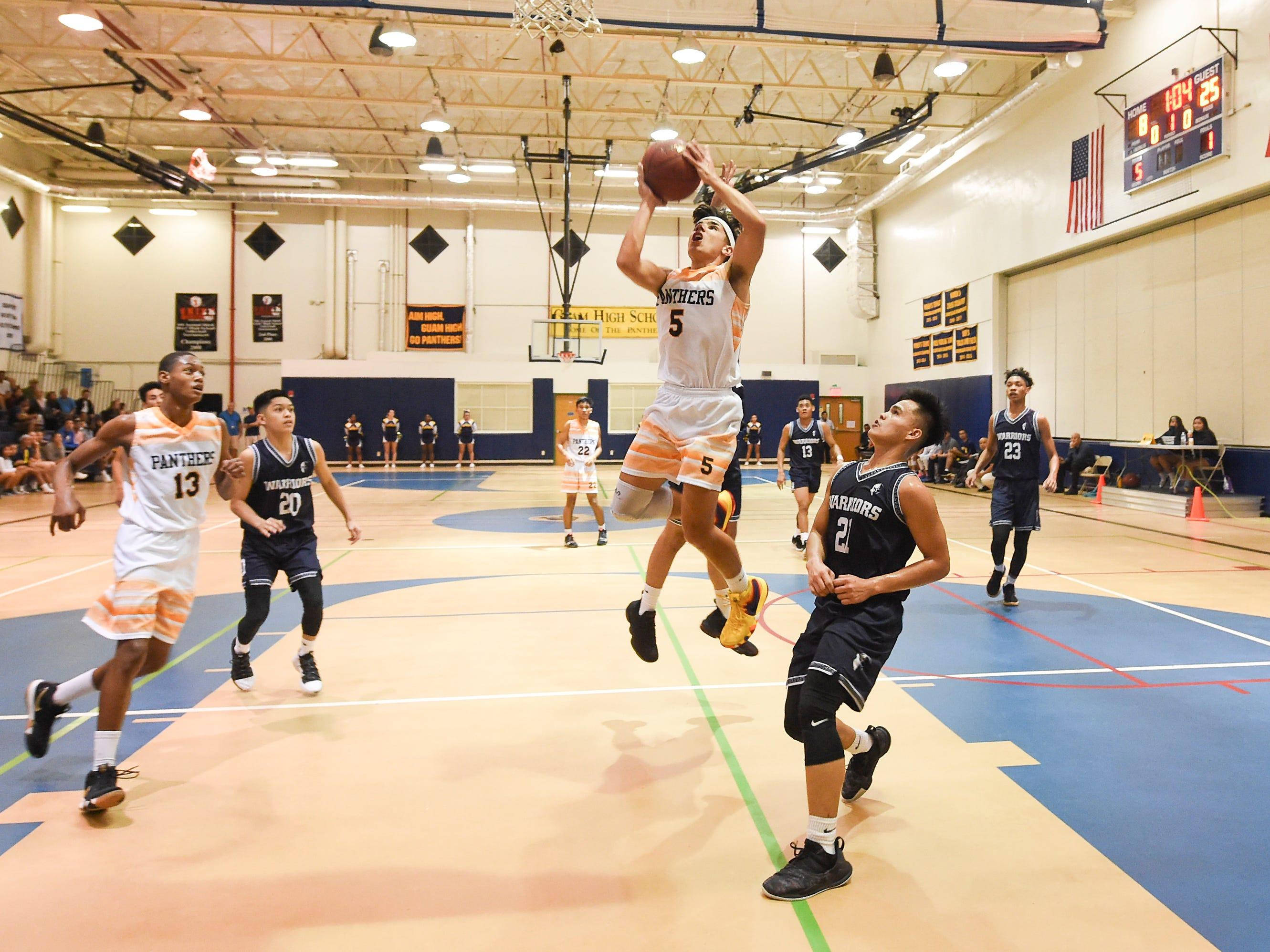 Guam High's Nicholas Keefe (5) attempts a shot against the St. Paul Warriors during their IIAAG Boys' Basketball game at the Guam High School Gym, Feb. 5, 2019.