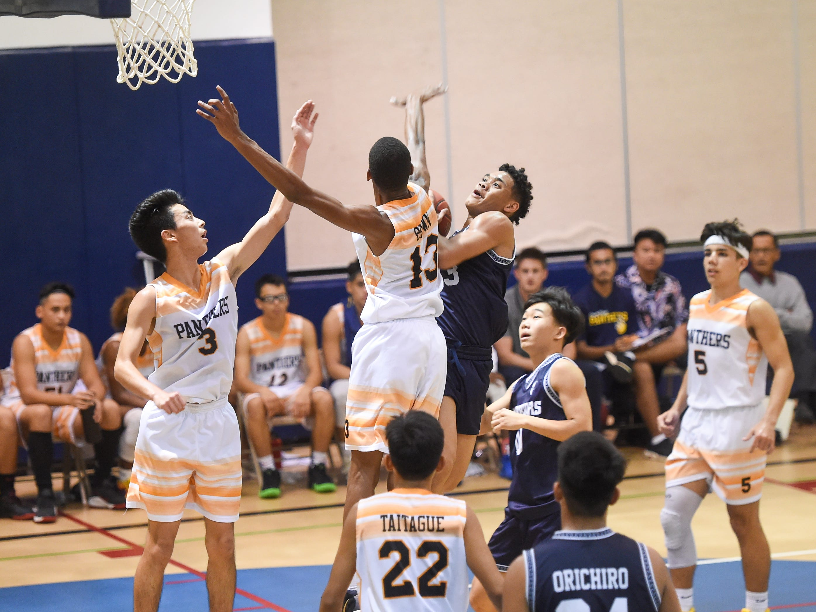 Guam High's Corey Brown (13) goes for a block on St. Paul's Jahmar White during their IIAAG Boys' Basketball game at the Guam High School Gym, Feb. 5, 2019.