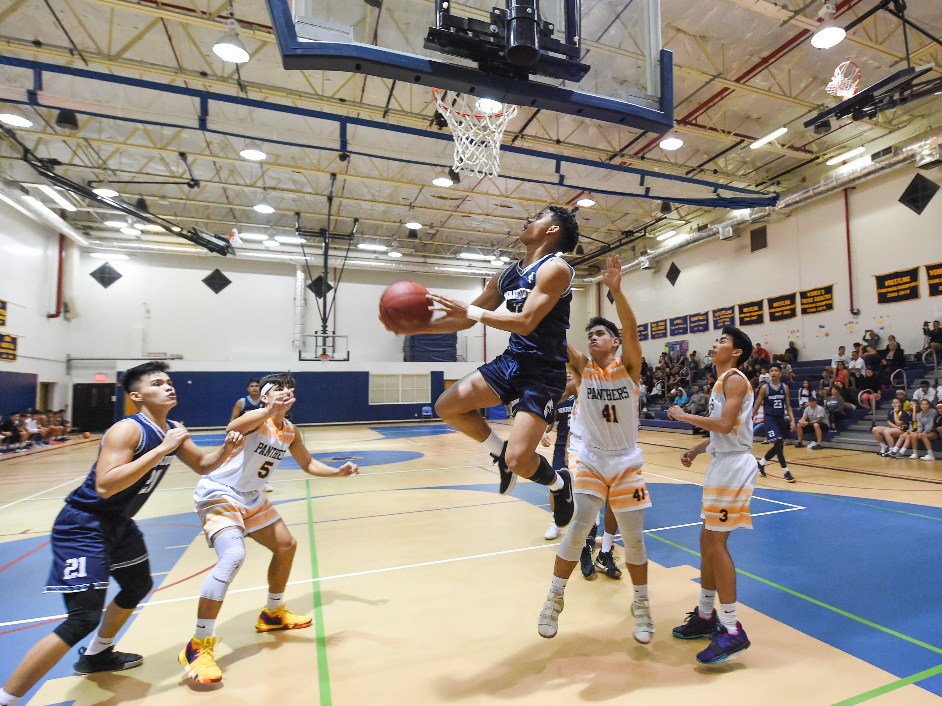 St. Paul's Jahmar White goes for a reverse layup against the Guam High Panthers during their IIAAG Boys' Basketball game at the Guam High School Gym, Feb. 5, 2019.