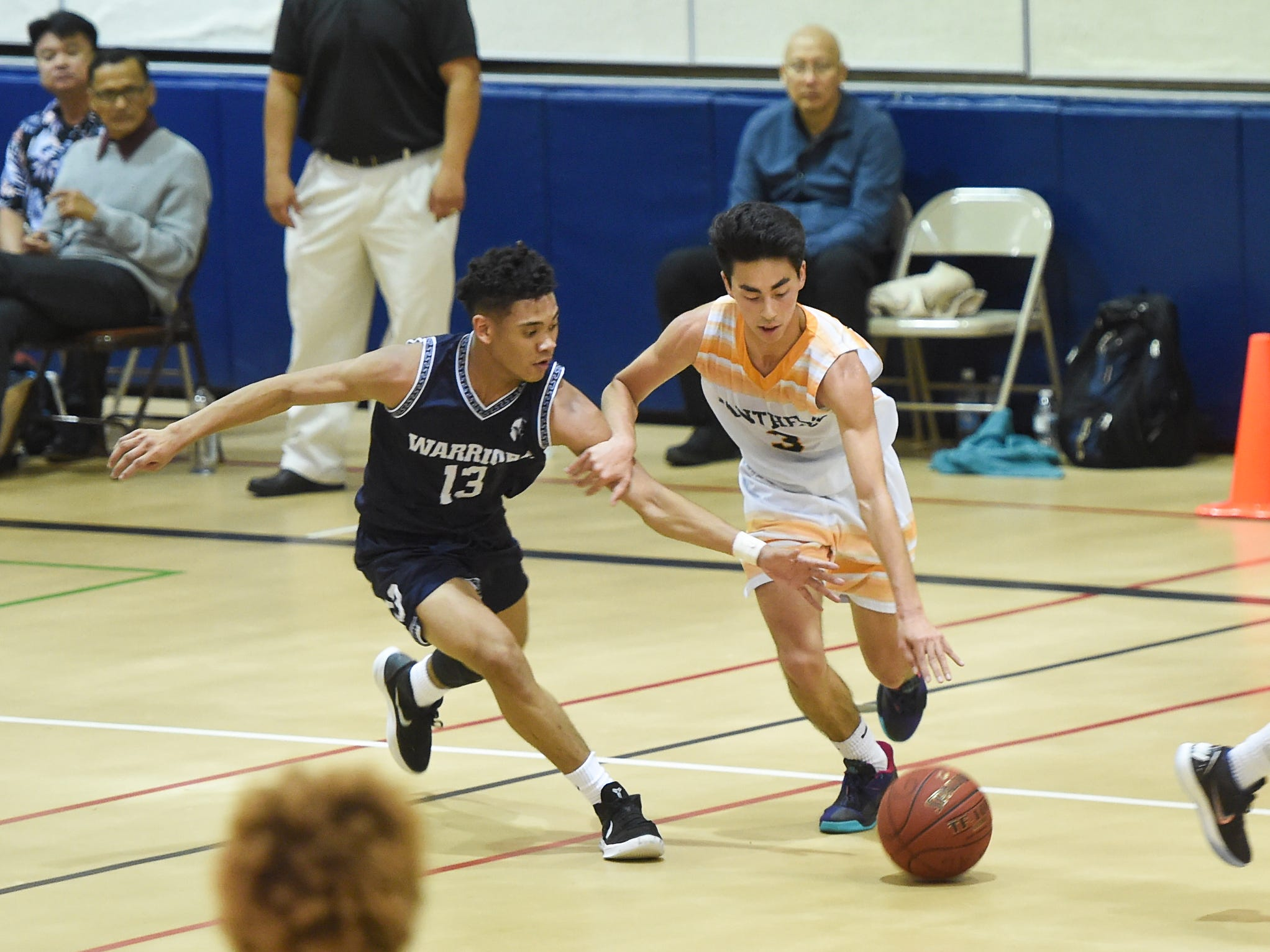 The Guam High Panthers' Akira Martines (3) protects the ball from St. Paul player Jahmar White (13) during their IIAAG Boys' Basketball game at the Guam High School Gym, Feb. 5, 2019.