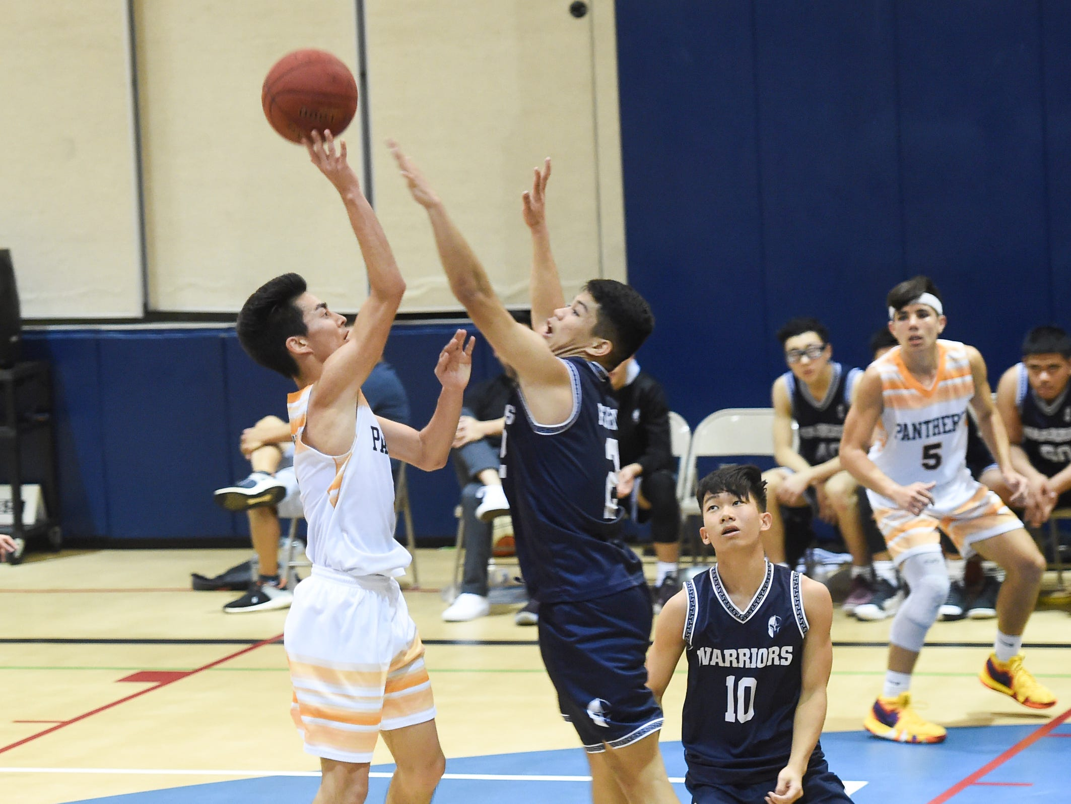 Guam High Panthers player Akira Martines drives to the basket against the St. Paul Warriors during their IIAAG Boys' Basketball game at the Guam High School Gym, Feb. 5, 2019.