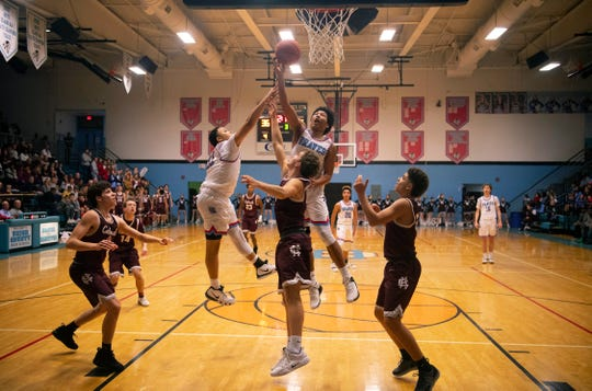 Union County's Kaleb Kanipe goes high to corral a rebound against Henderson County at Union County High School Monday night.