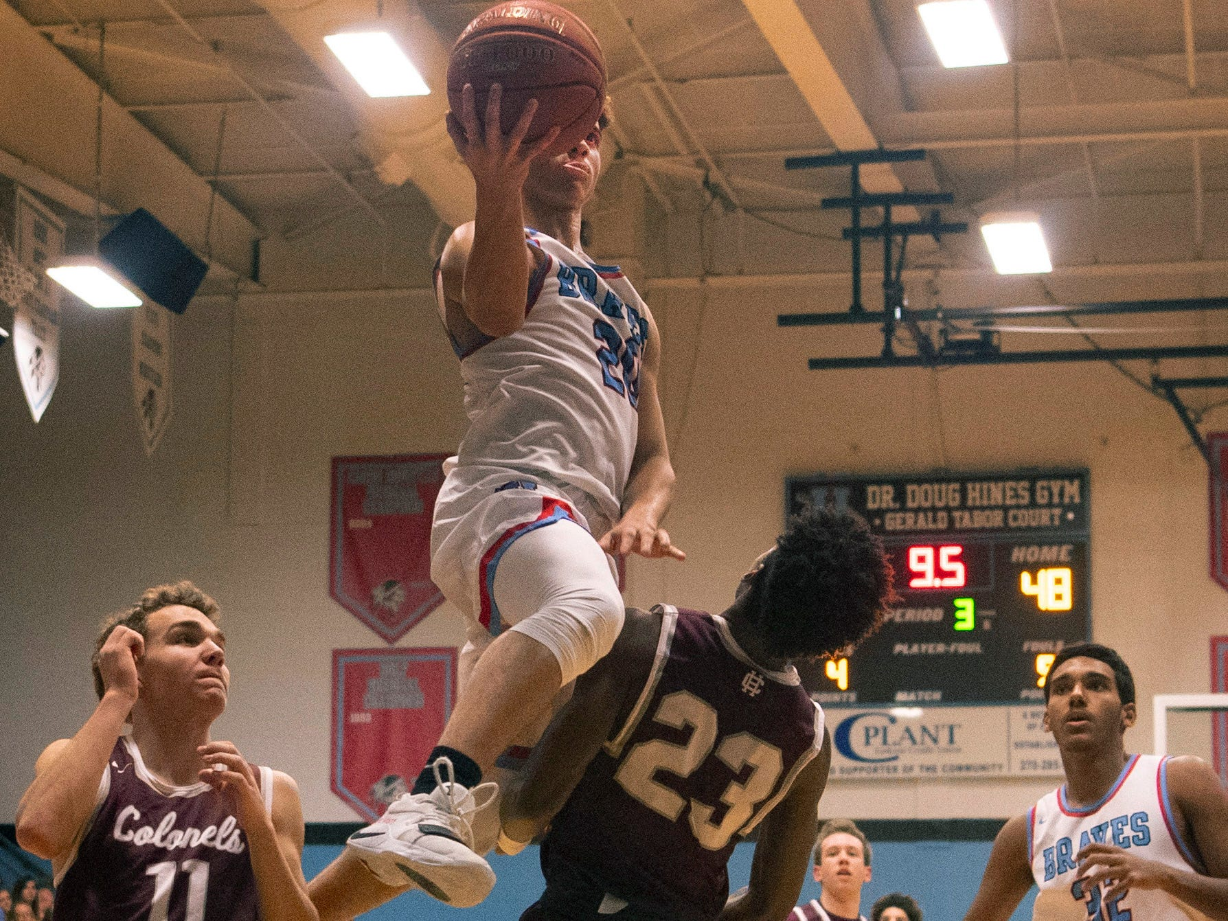 Union County's Kale Gaither (20) goes up for a layup against Henderson County's Myekel Sanners (23) at Union County High School Monday night. Sanners was called for a blocking foul on the play.