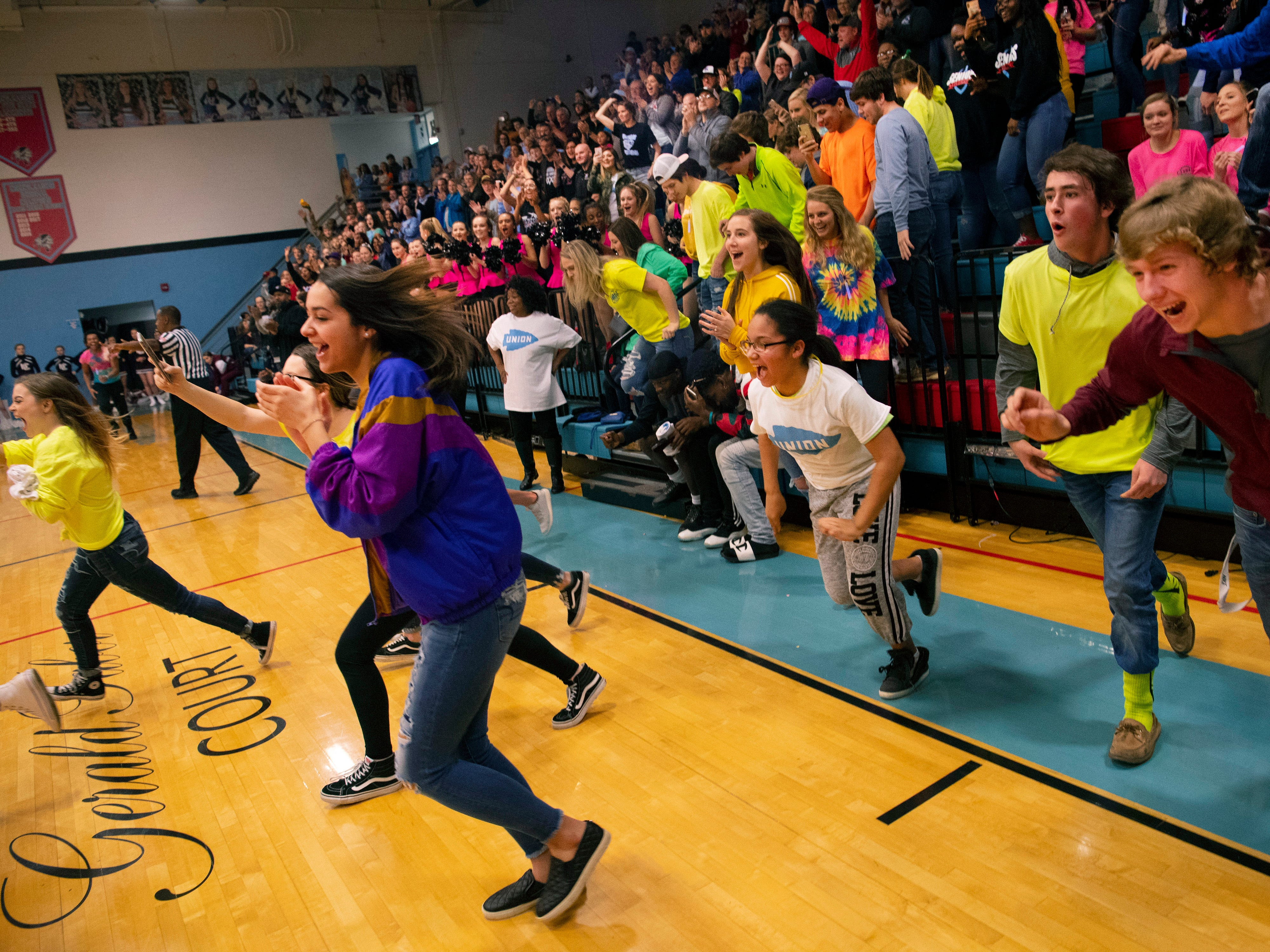 The Union County student section spills onto the floor after their boys basketball team salted away the game against Henderson County at Union County High School Monday night. The Braves snapped their 16-game losing streak against the Colonels.