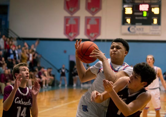 Union County's Keishon Martin pulls down a rebound against Henderson County's Holden Raley (14) and Corey Stewart (1) at Union County High School Monday night.