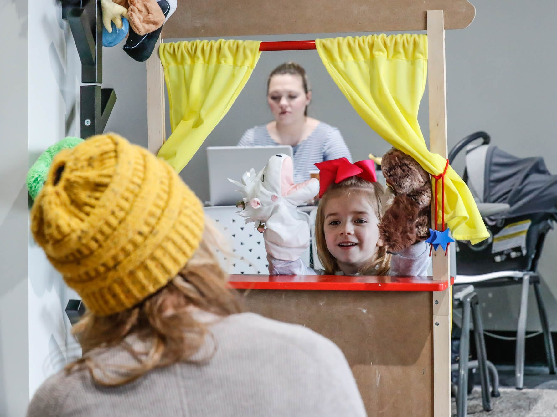 Ali Coulom, left, and her daughter Leslie Coulom play with a puppet theatre at The Little Village Playroom, 9850 N. Michigan Rd, Carmel, Ind., on Tuesday, Feb. 5, 2019. Behind, Mom Emelie Russell works on her computer while watching her child.