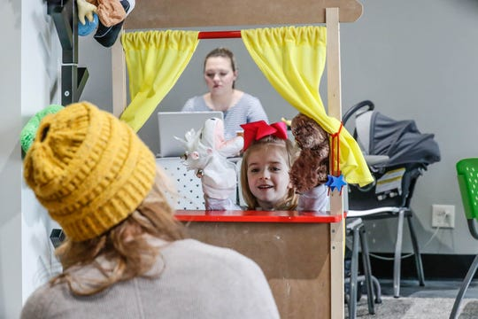 Ali Coulom and her daughter Leslie play with a puppet theater at The Little Village Playroom in Carmel.