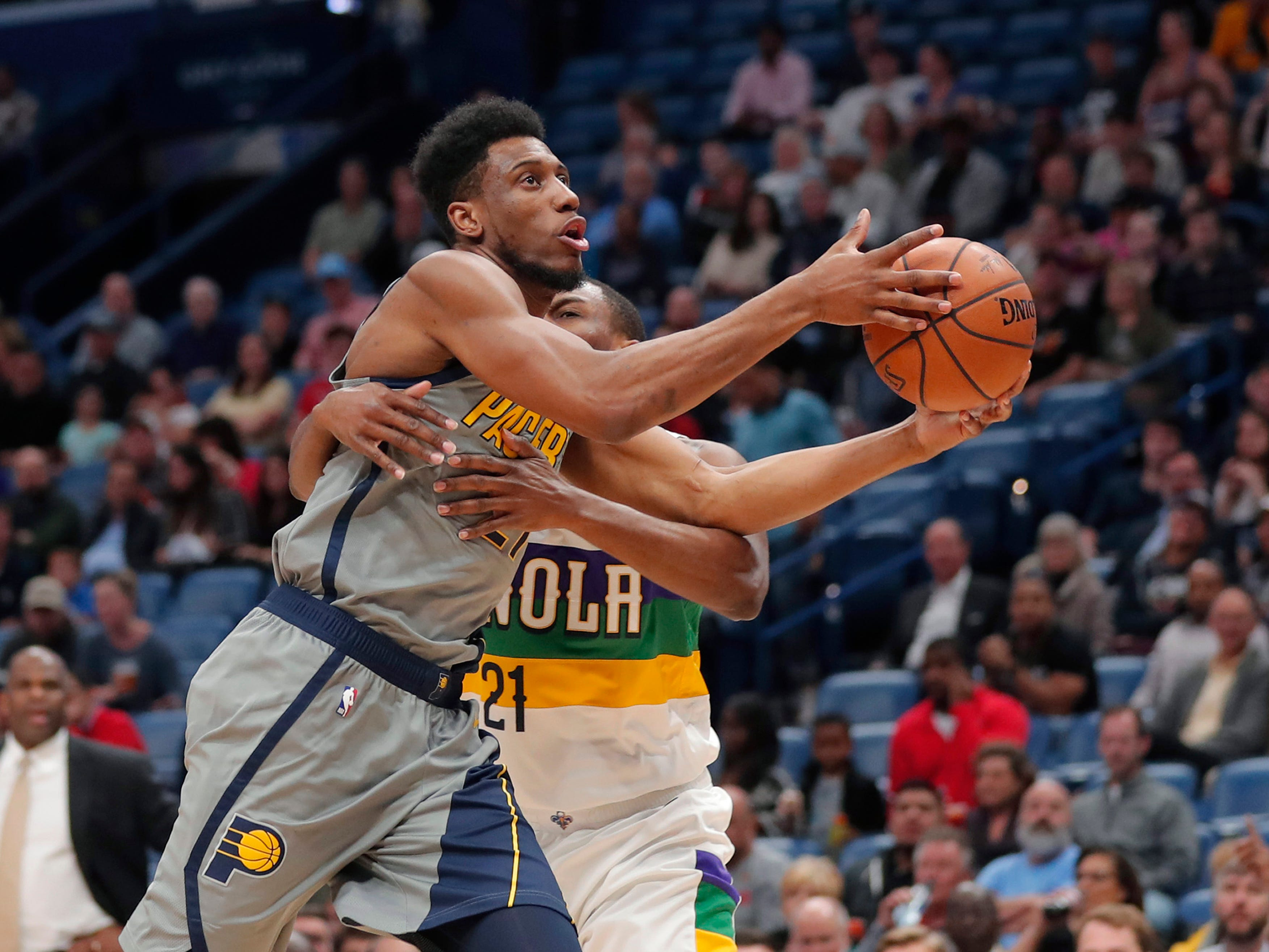 Indiana Pacers forward Thaddeus Young (21) is fouled by New Orleans Pelicans forward Darius Miller as he drives to the basket in the first half of an NBA basketball game in New Orleans, Monday, Feb. 4, 2019.
