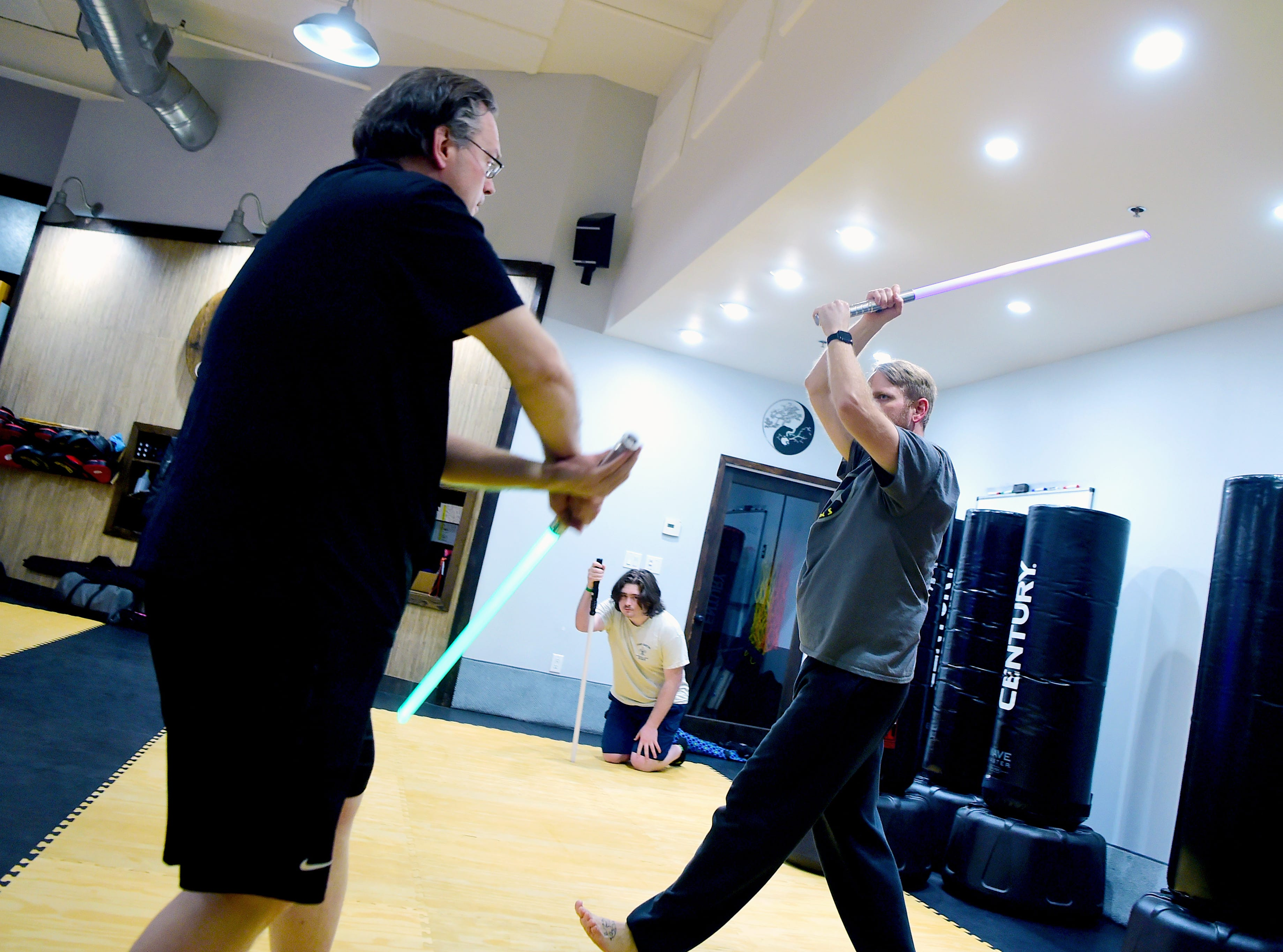 Ithaca Sabers instructor Ben Judkins, left, works with Terry Gray, right, of Lansing, during the group's weekly lightsaber combat session at Centerline Fitness & Martial Arts in Ithaca.  February 4, 2019.