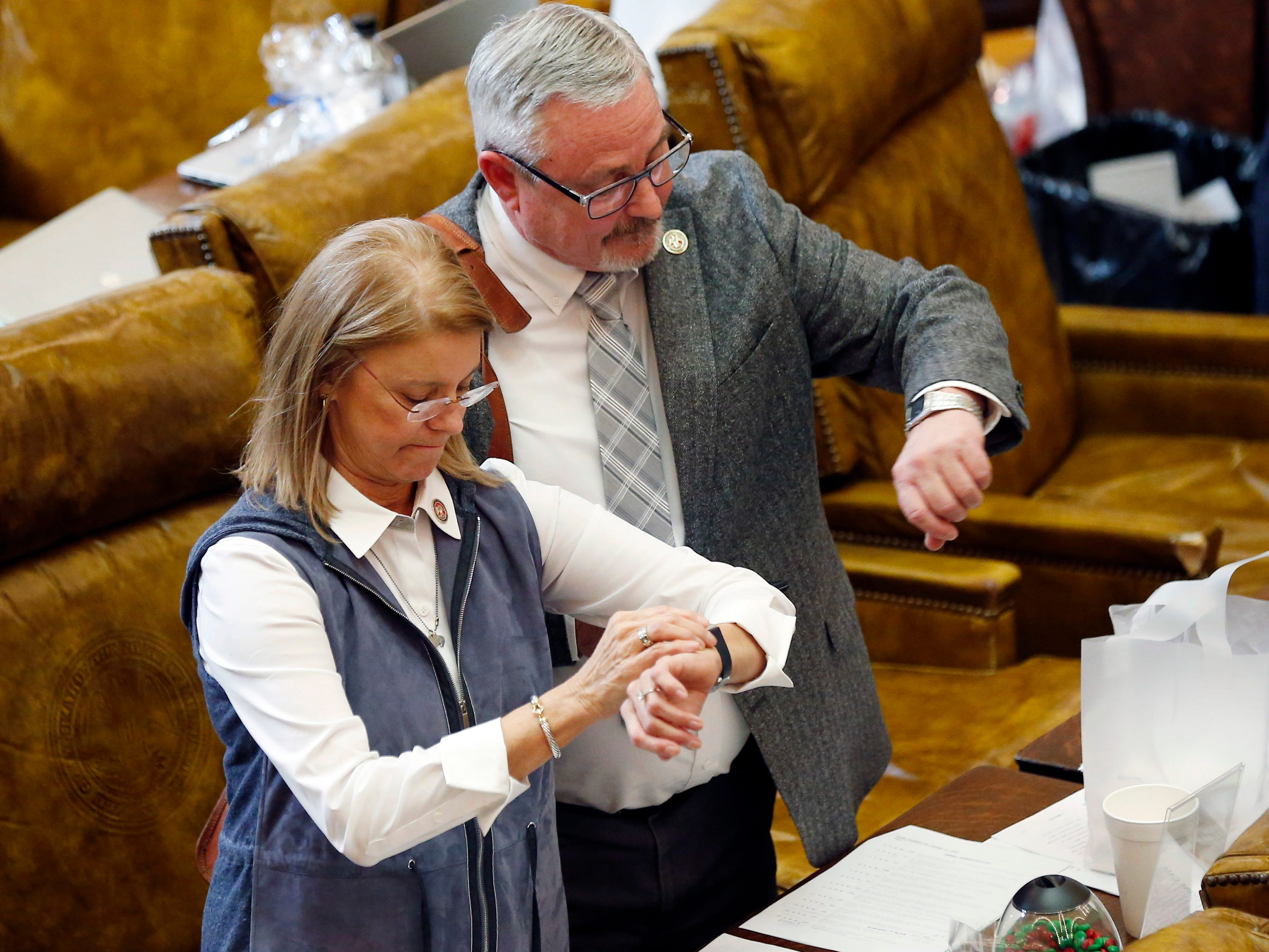 Republican Reps. Patricia Willis, R-Diamondhead, left, and Bill Kinkade, R-Byhalia Capitol in Jackson, Miss., synchronize their watches at adjournment, Thursday, Jan. 31, 2019.