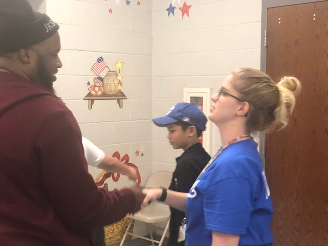 Anthony Cuyler, founder of the mentoring program Hugs & Hustle, greets students and teachers after a Black History Month kickoff event Thursday. Cuyler is also an 18-year volunteer coach. He spoke about Jackie Robinson and his life, legacy and character during a time of segregation and adversity.