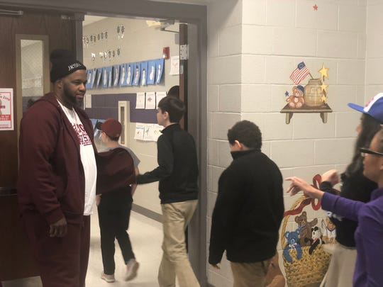 Anthony Cuyler, founder of mentoring program Hugs & Hustle, greets students and teachers after a Black History Month kickoff event Thursday. He spoke about Jackie Robinson and his life, legacy and character.