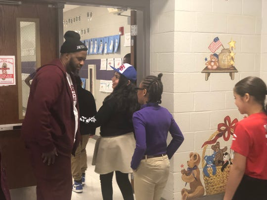 Anthony Cuyler, founder of mentoring program Hugs & Hustle, greets students and teachers after a Black History Month kickoff event Thursday.