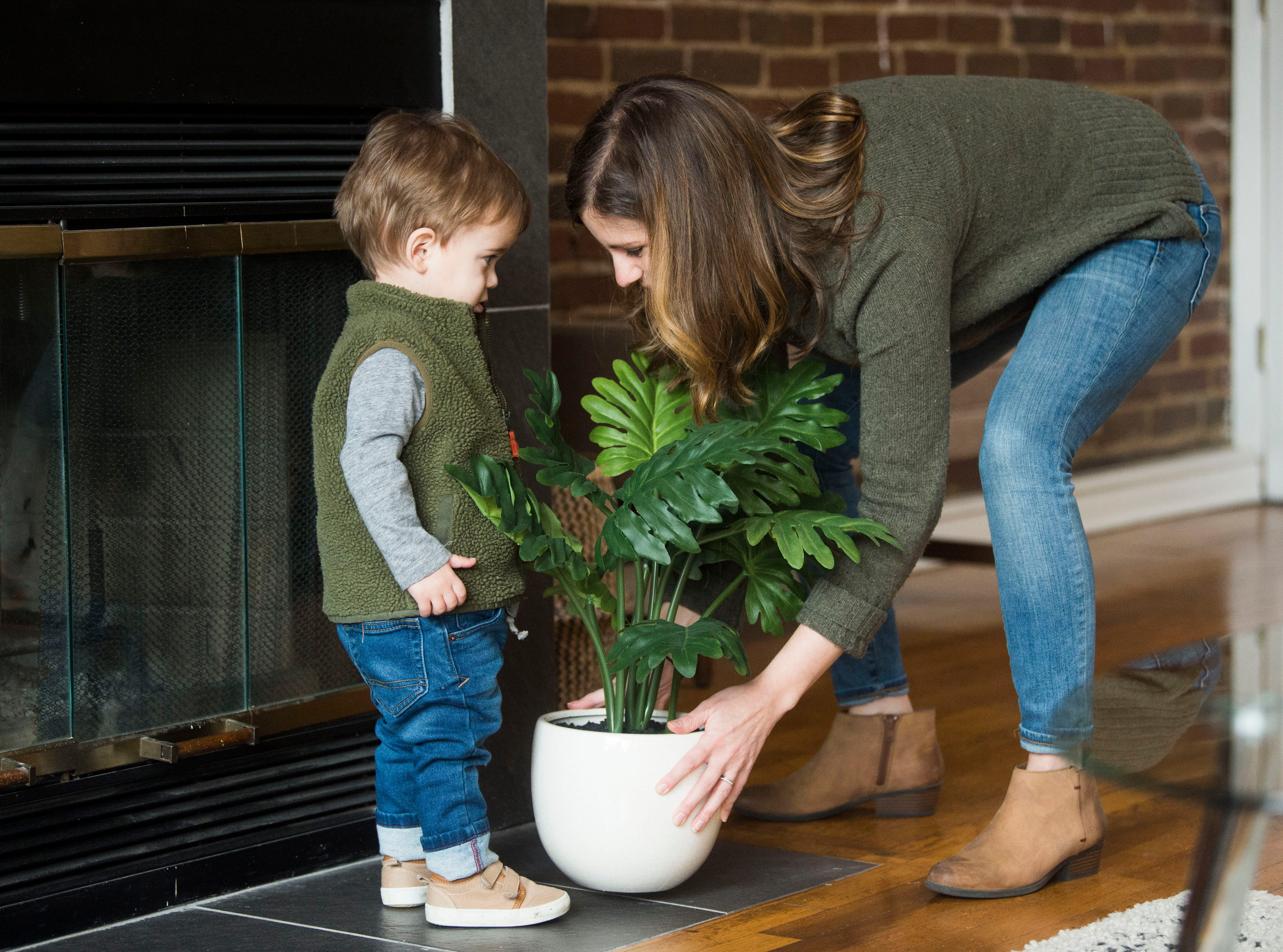 Suzanne Robinson straightens a potted plant with her 21-month-old son Duke at one of 14 short-term rental properties her and her husband Dylan manage in their company Knox Staytion, in Old City Tuesday, Feb. 5, 2019.