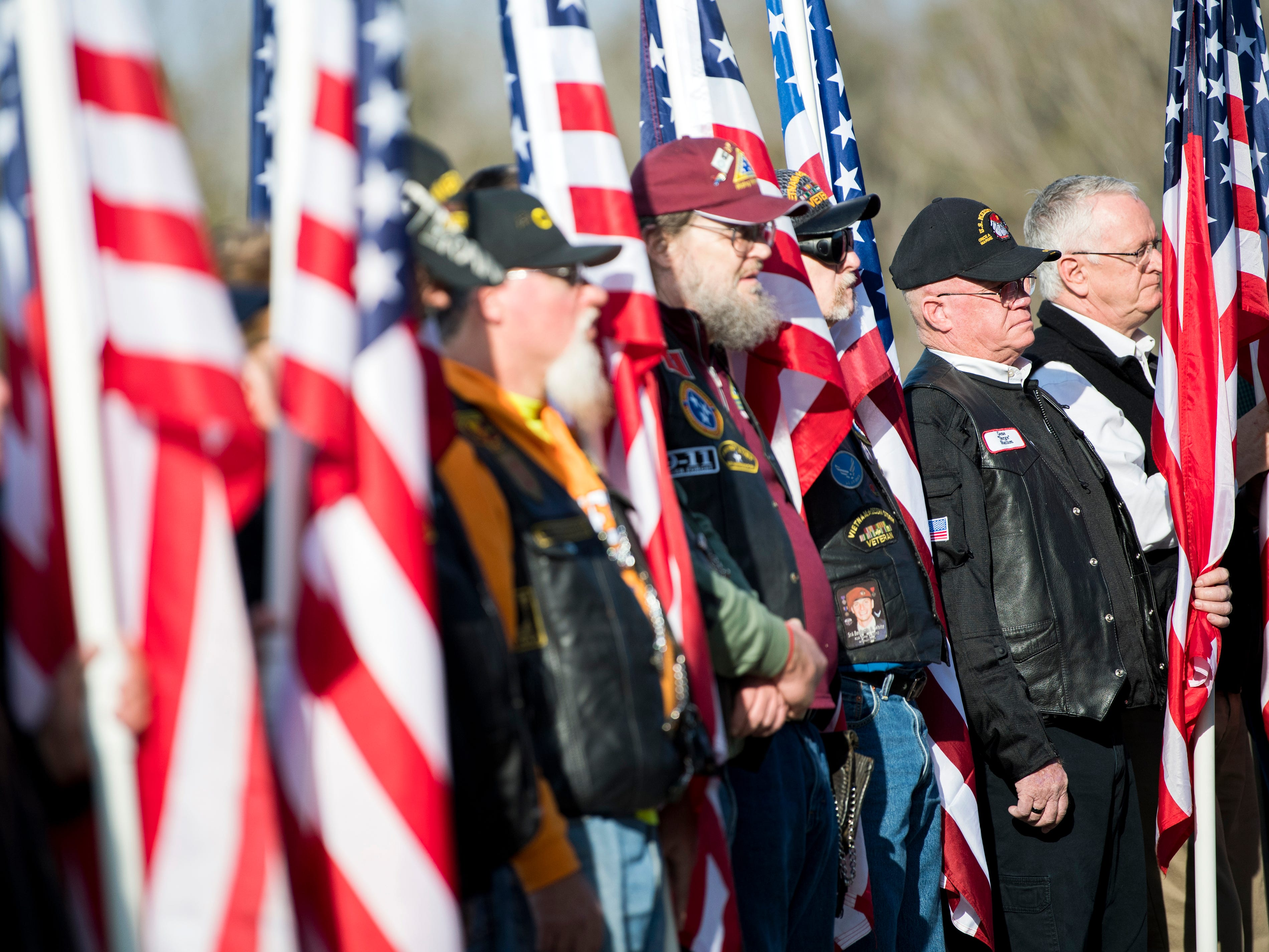 Veterans hold American flags during a military memorial service for seven East Tennessee veterans held at the East Tennessee Veterans Cemetery on Gov. John Sevier Highway on Tuesday, February 5, 2019.
