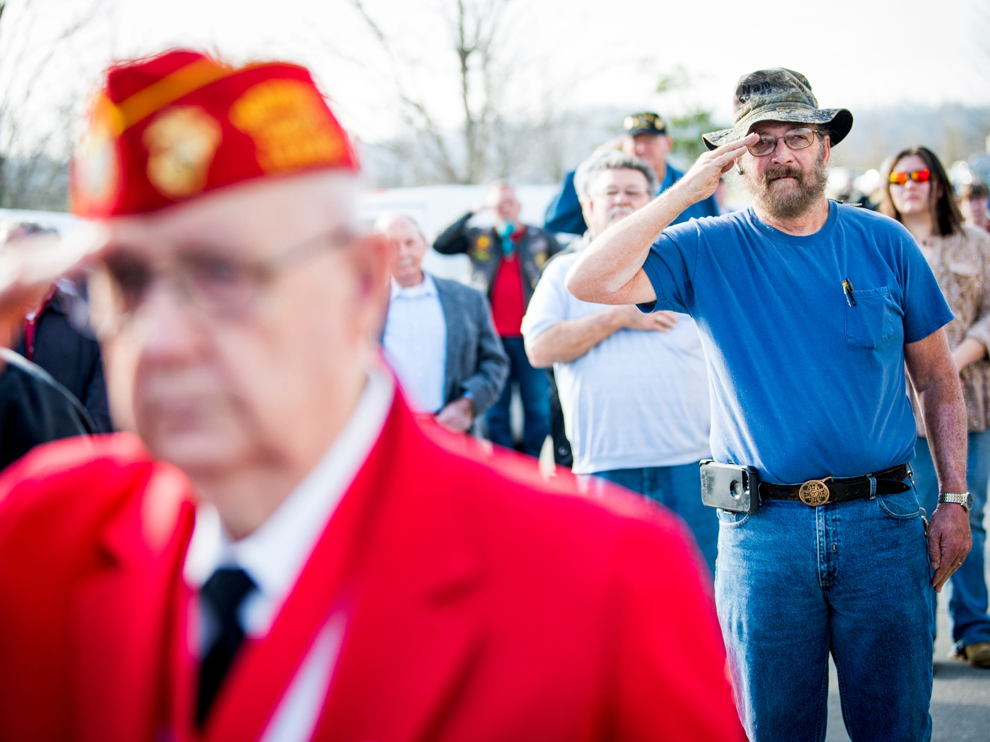 Veterans salute as Taps is played during a military memorial service for seven East Tennessee veterans held at the East Tennessee Veterans Cemetery on Gov. John Sevier Highway on Tuesday, February 5, 2019.