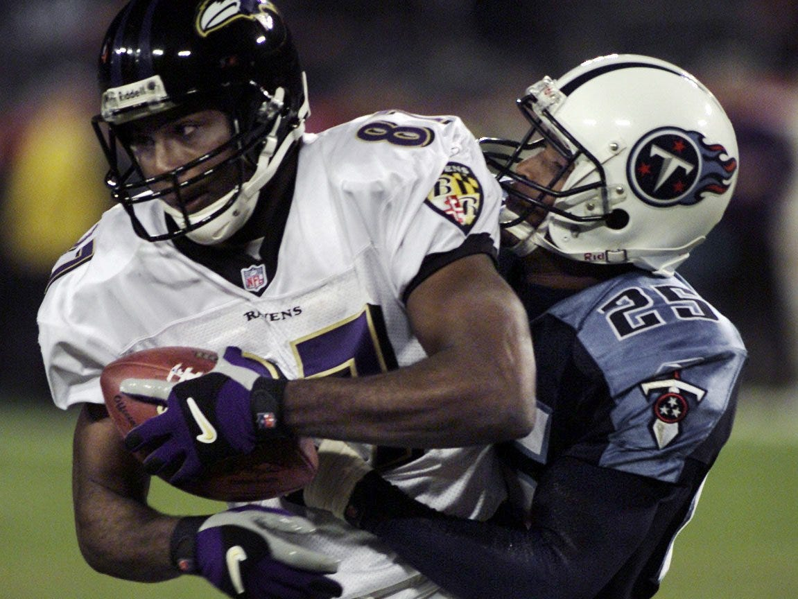 Ravens wide receiver Qadry Ismail is taken down by Titans corner back DeRon Jenkins during the first quarter.