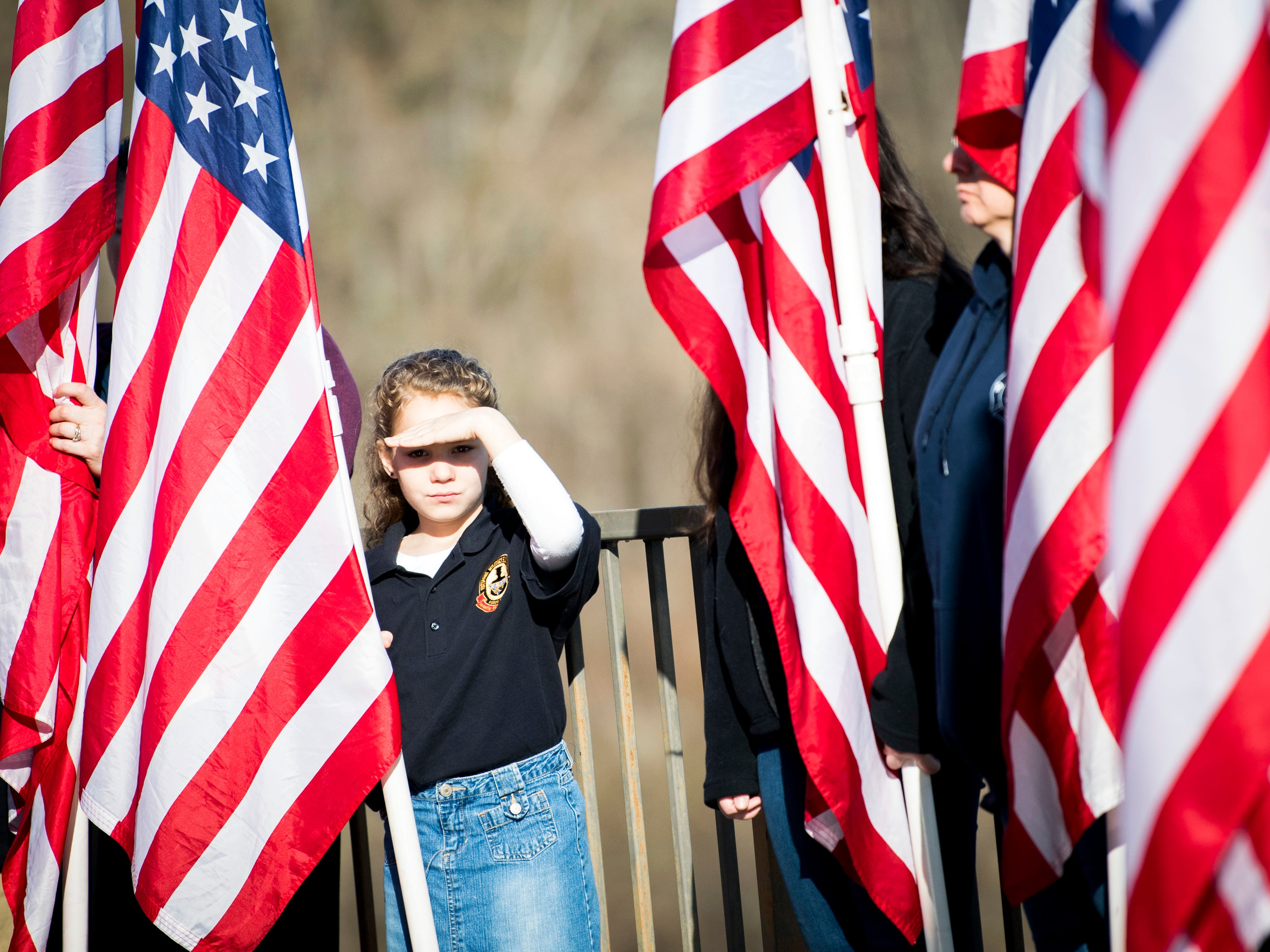 A child holds up an American flag during a military memorial service for seven East Tennessee veterans held at the East Tennessee Veterans Cemetery on Gov. John Sevier Highway on Tuesday, February 5, 2019.