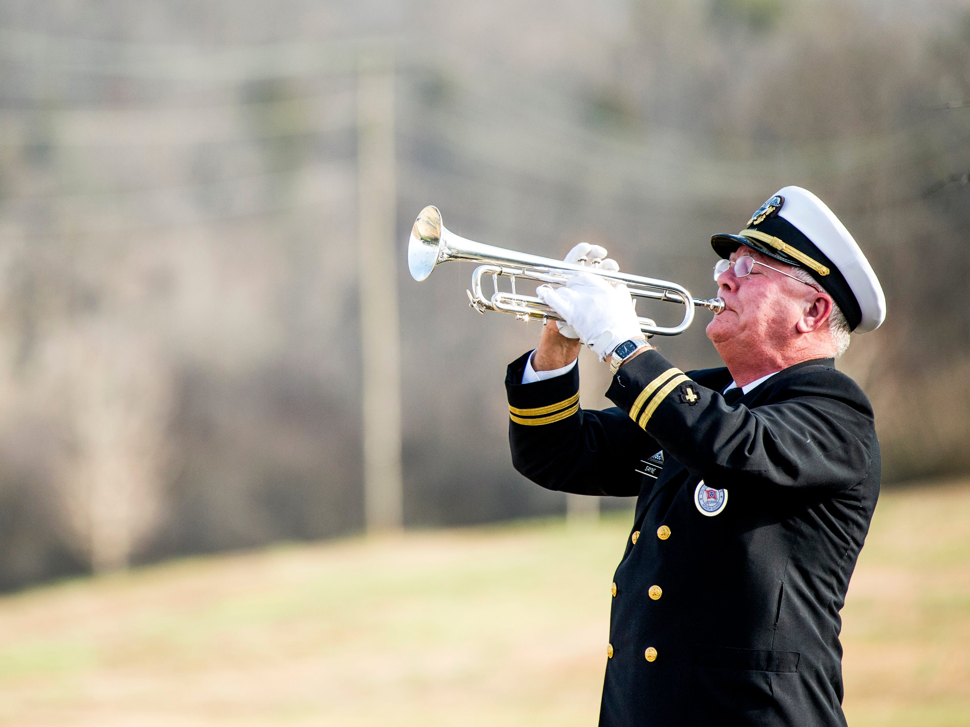 "A trumpeter plays ""Taps"" during a military memorial service for seven veterans held at the East Tennessee Veterans Cemetery on Gov. John Sevier Highway on Tuesday, February 5, 2019."