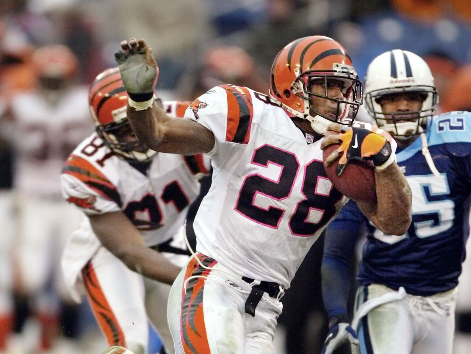 Text: Cincinnati Bengals' half back Corey Dillon (28) moves past Tennessee Titans' cornerback DeRon Jenkins (25) on a 34-yard touchdown run in the second quarter on Sunday, Jan. 6, 2002 in Nashville, Tenn. At left is Bengals' wide receiver Ron Dugans (81).