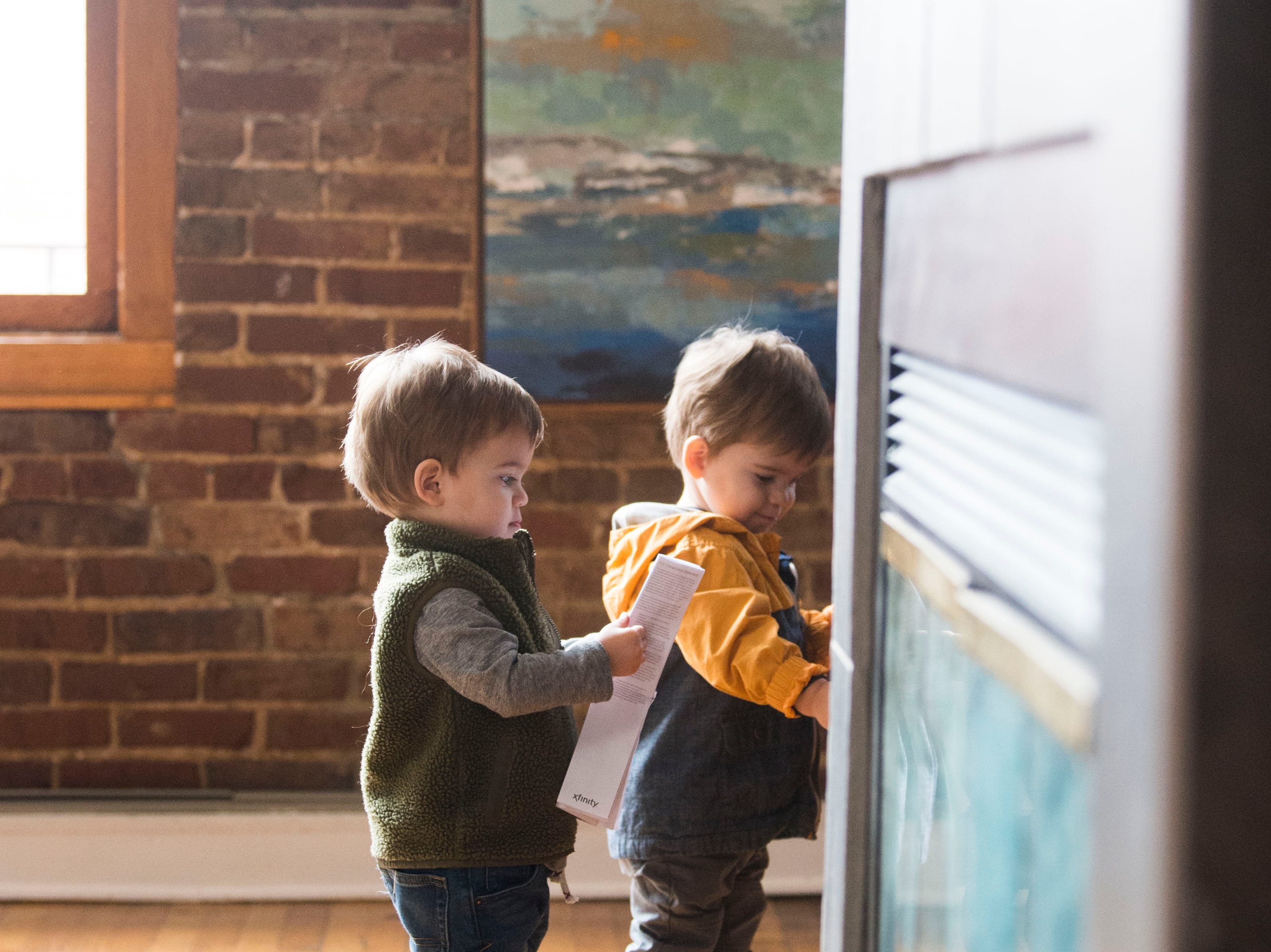 From left 21-month-old twins Duke and Pete Robinson explore one of the 14 short-term rental properties their parents Suzanne and Dylan Robinson manage in their company Knox Staytion, in Old City Tuesday, Feb. 5, 2019.