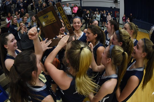 Central Catholic players swarm the sectional trophy in celebration following their championship win Monday night.