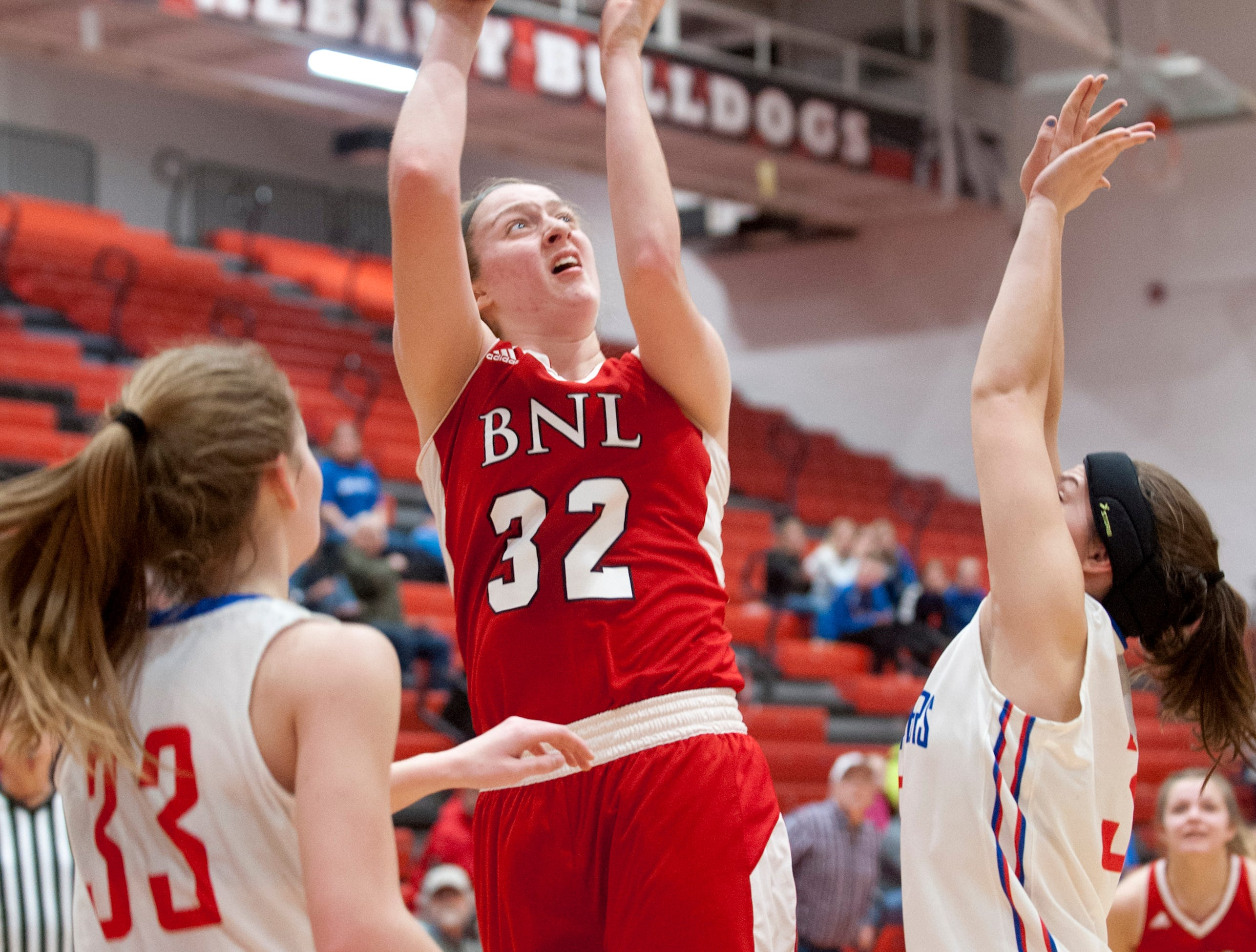 Bedford North Lawrence center Madison Webb puts up a shot between Jennings County guard-forward Lily Ernstes, left, and Jennings County guard-forward McKenna Maschino, right.04 February 2019