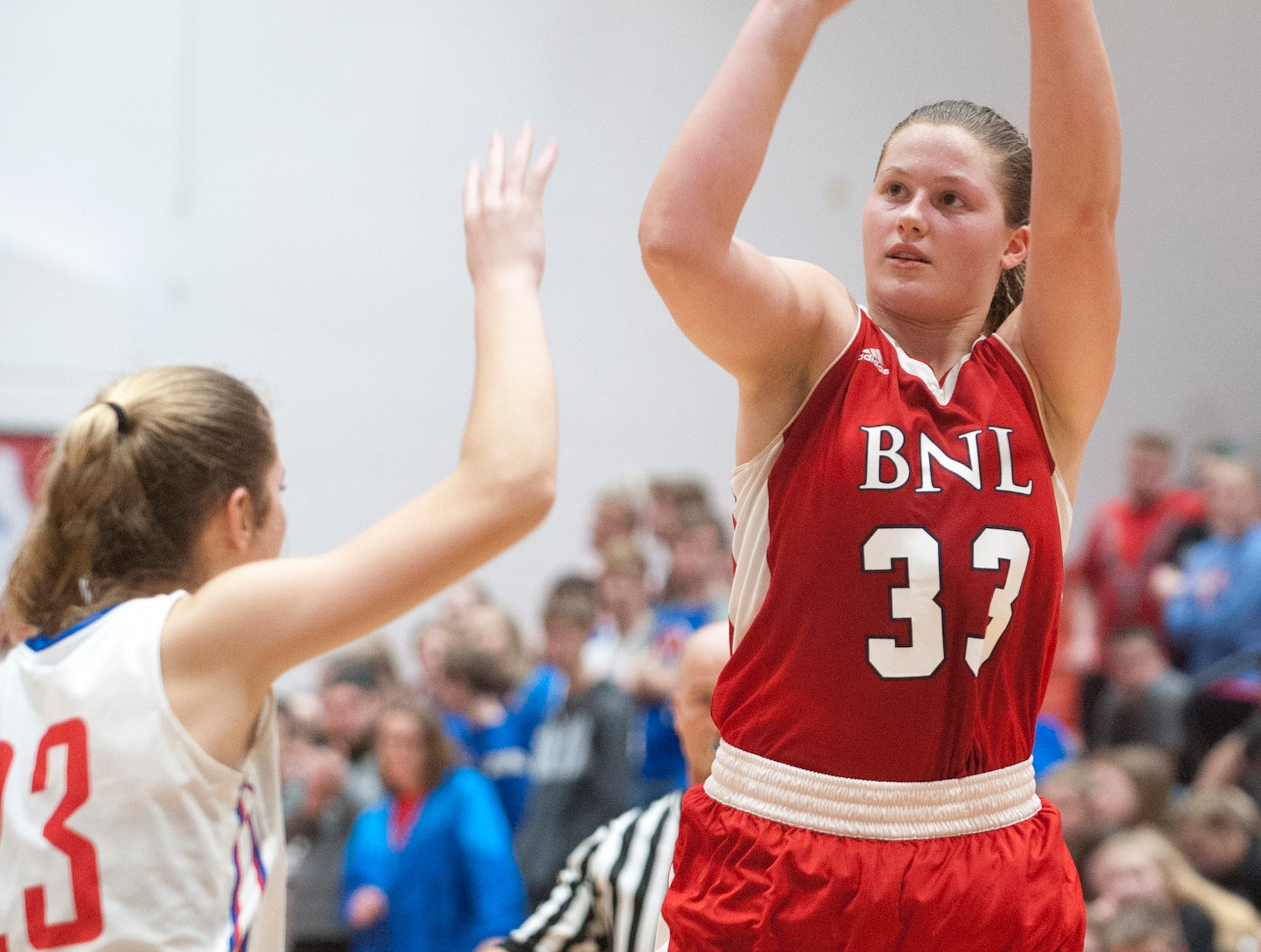 Bedford North Lawrence forward Jorie Allen puts up a 3-point who over Jennings County center-forward Callie Wilder, left.04 February 2019