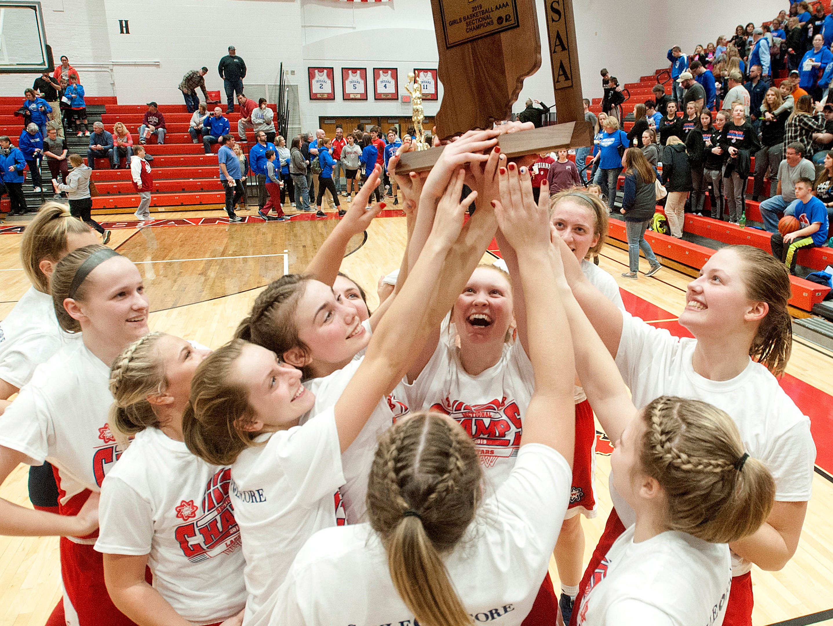 The Bedford North Lawrence girls basketball team hold their trophy high after defeating Jennings County in the IHSAA New Albany Sectional Championship 56-34.05 February 2019