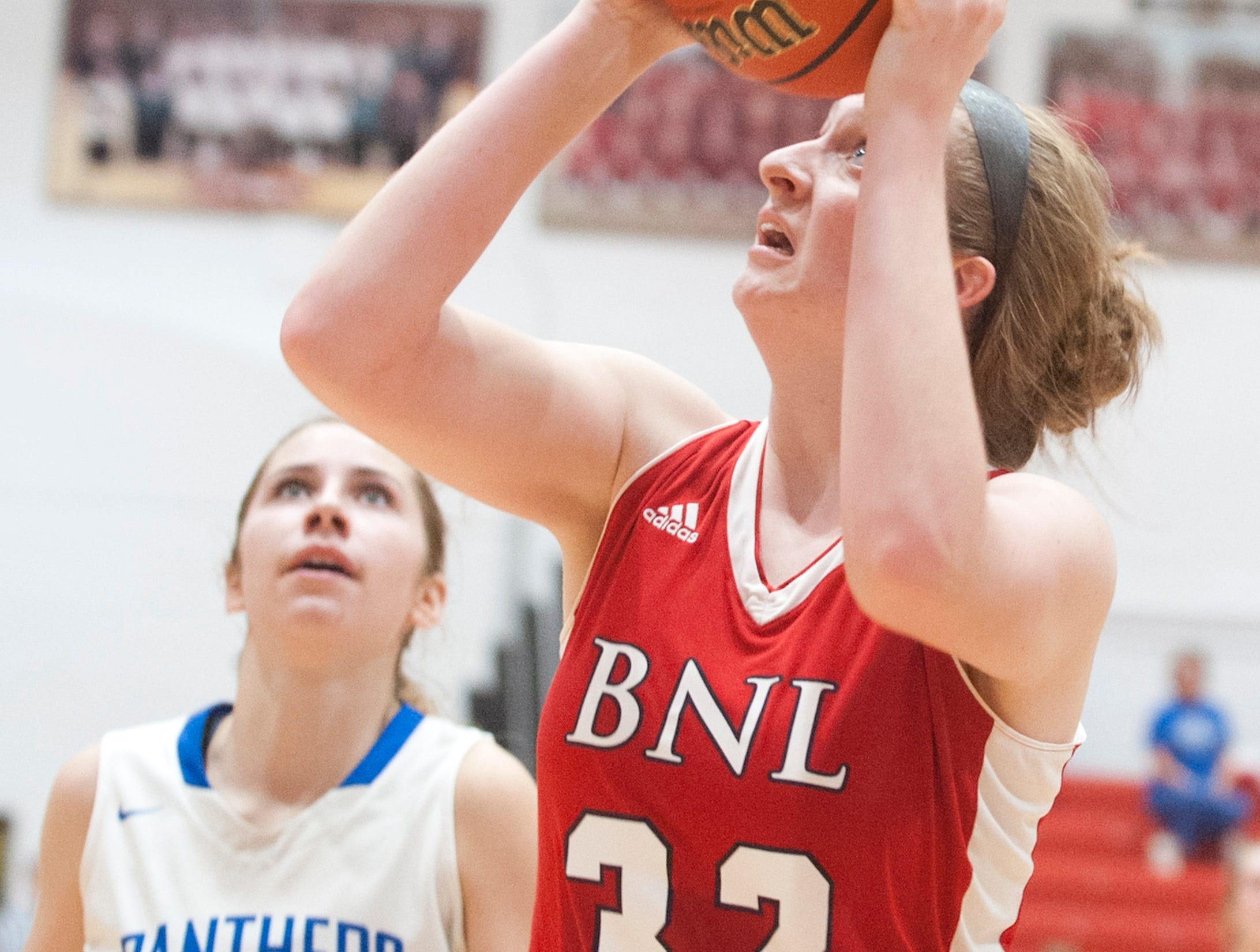 As Jennings County center Grace Ramey watches, left, Bedford North Lawrence center Madison Webb puts up a shot.04 February 2019