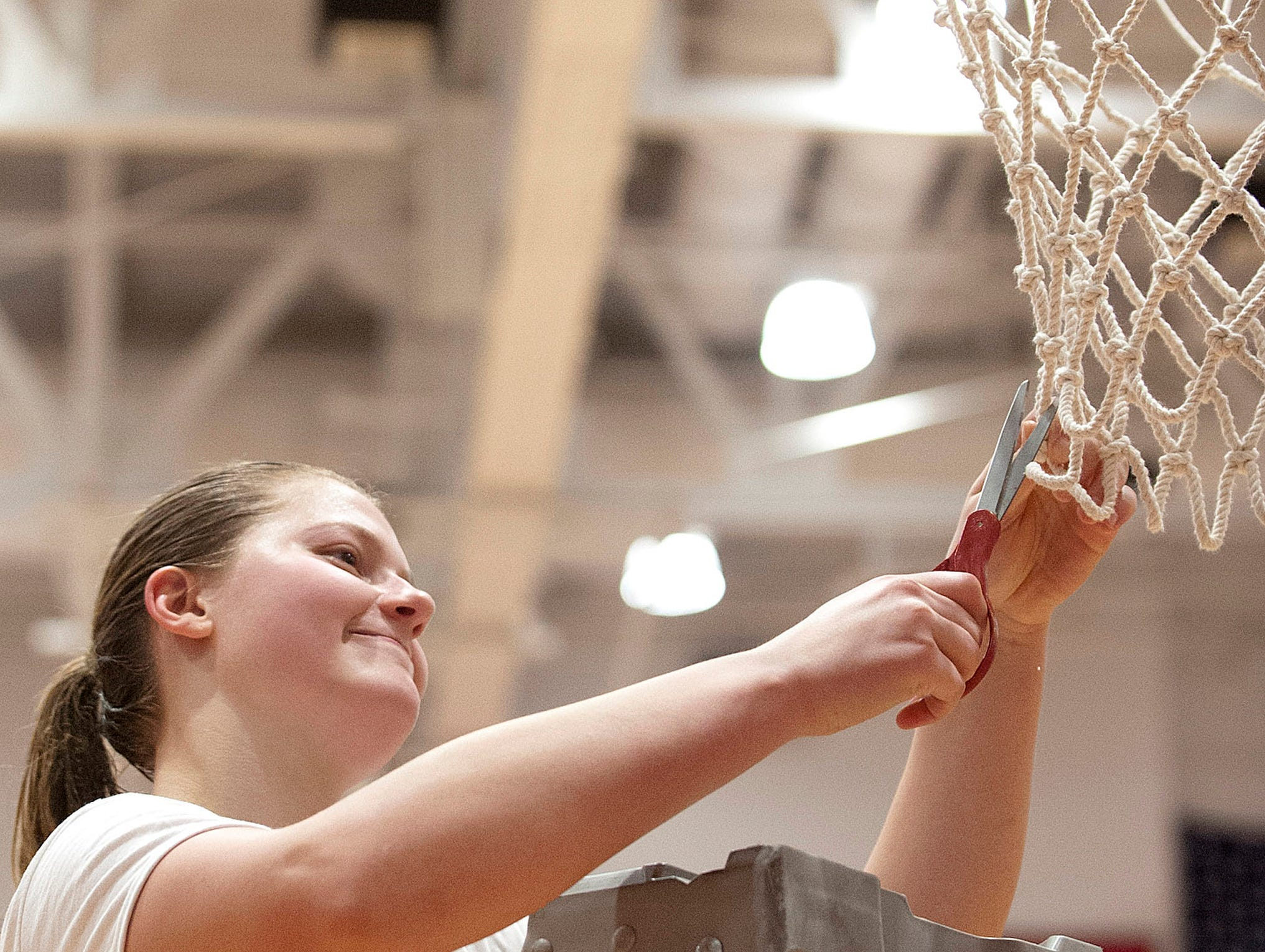 Bedford North Lawrence forward Jorie Allen cuts down the net after her team defeated Jennings County in the IHSAA New Albany Sectional Championship 56-34. Allen scored a team-high 17 points in the contest.05 February 2019