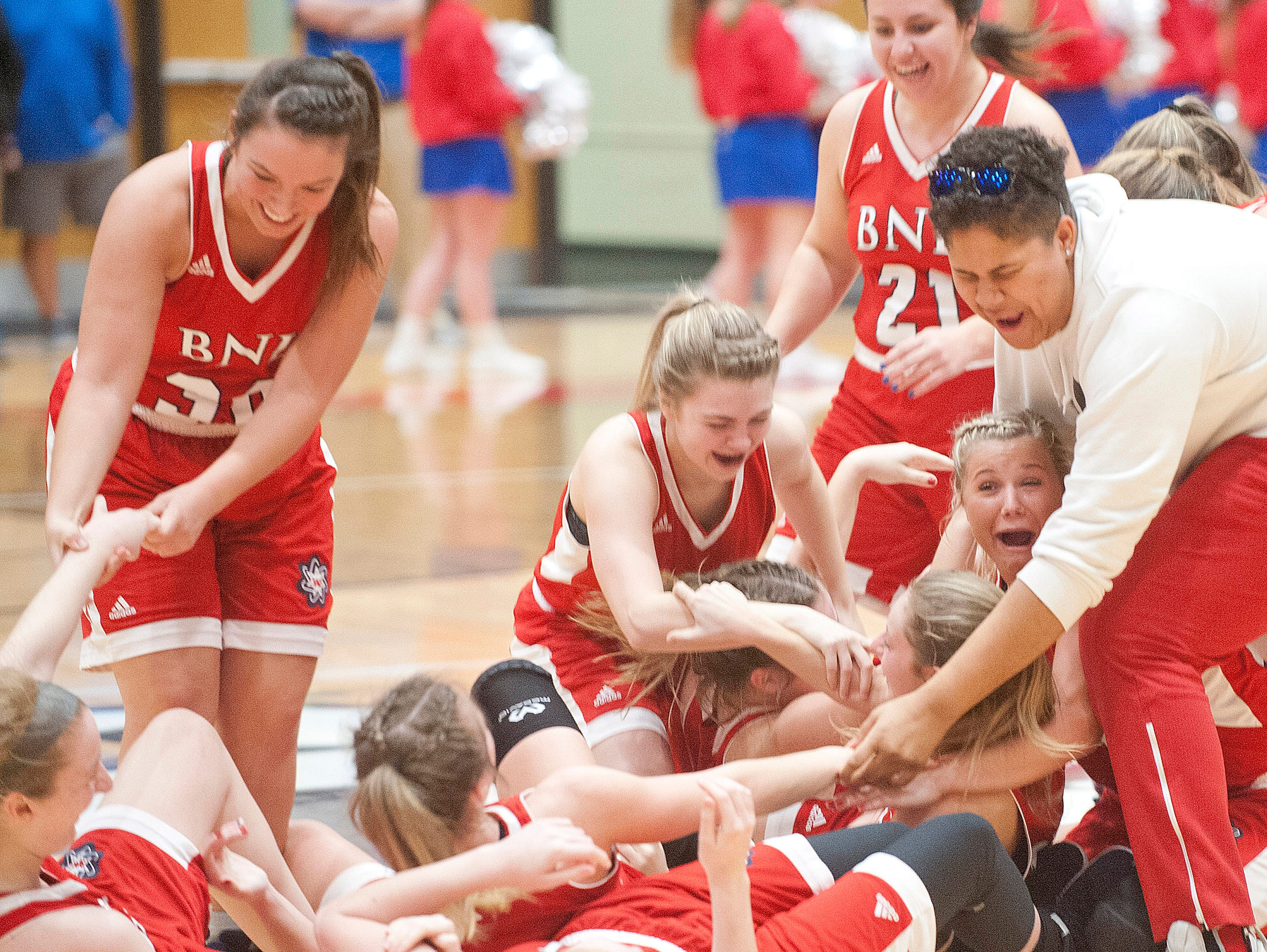 The Bedford North Lawrence girls basketball team piles onto each other moments after defeating Jennings County in the IHSAA New Albany Sectional Championship 56-34.05 February 2019