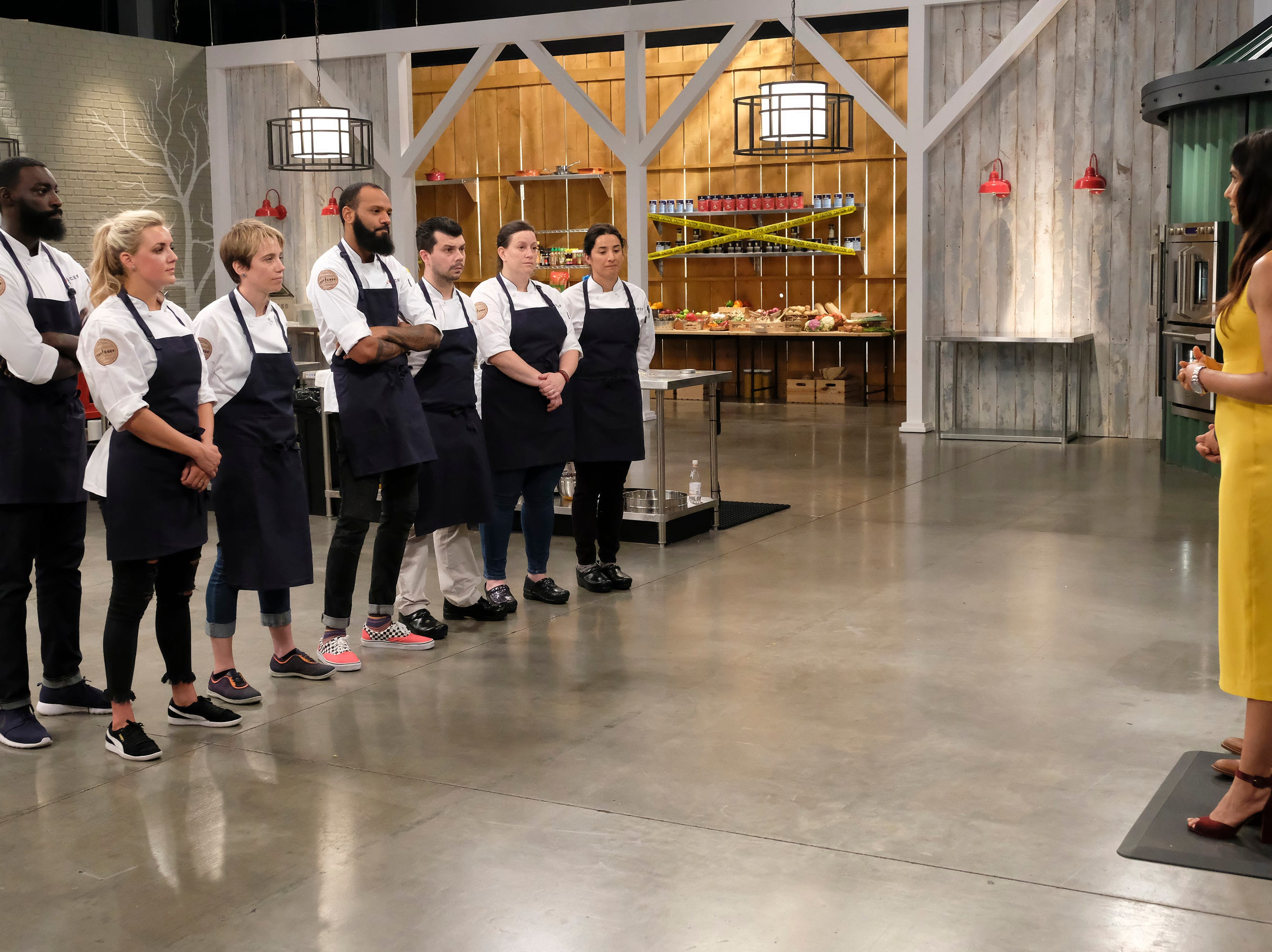 (From left to right): Contestants Eric Adjepong, Kelsey Barnard, Adrienne Wright, Justin Sutherland, Eddie Konrad, Sara Bradley and Michelle Minori listen to directions from host Padma Lakshmi on episode 10 of Bravo's 'Top Chef: Kentucky' season.